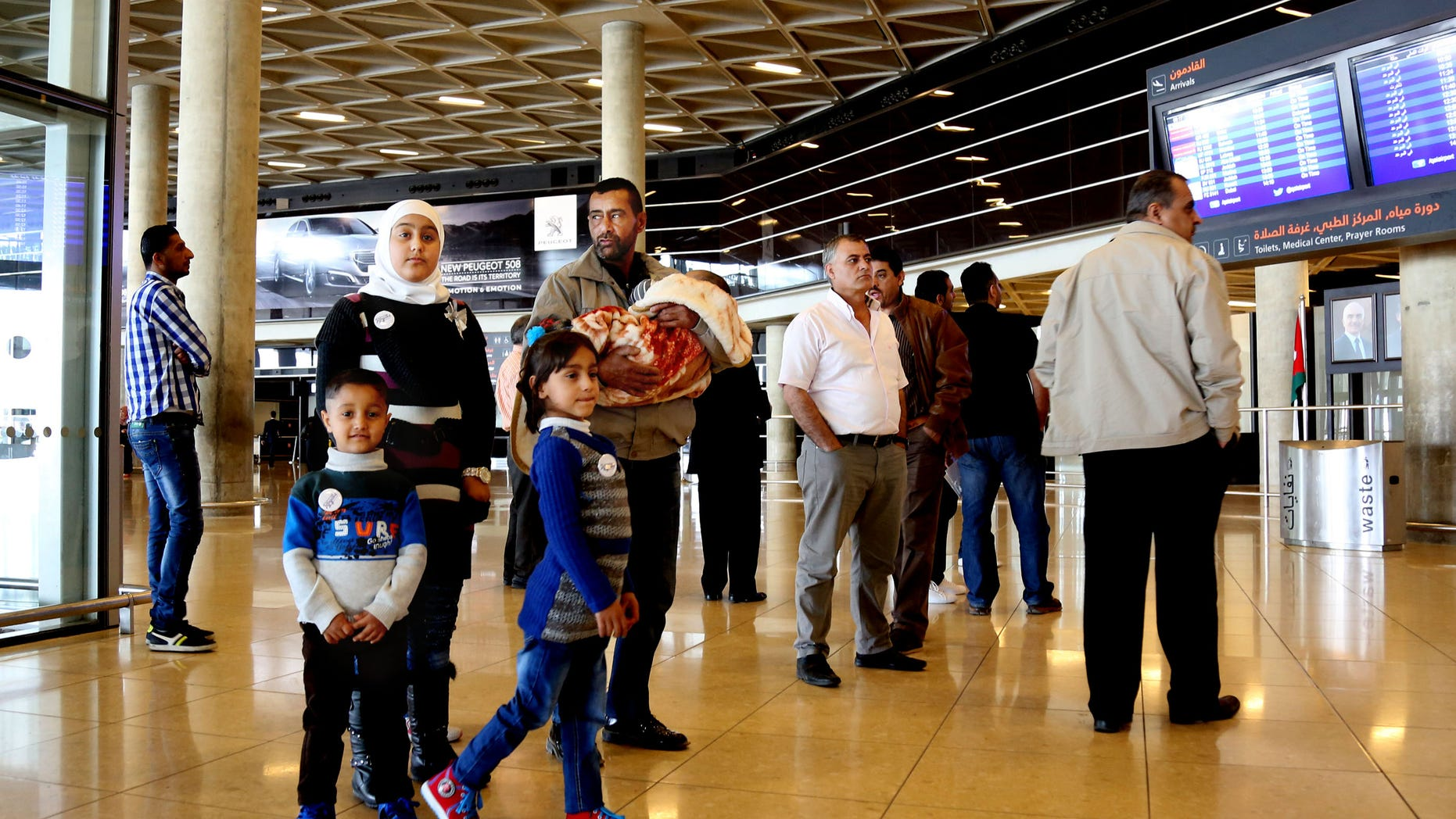 Syrian refugee Ahmad al-Abboud, center, waits with his family at the International Airport of Amman.