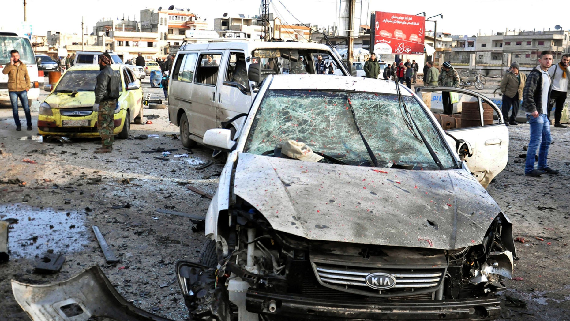 Jan. 26, 2016: In this photo released by the Syrian official news agency SANA, Syrian citizens gather at the scene where twin bombs exploded at a government-run security checkpoint, at the neighborhood of Zahraa, in Homs province, Syria. (SANA via AP)