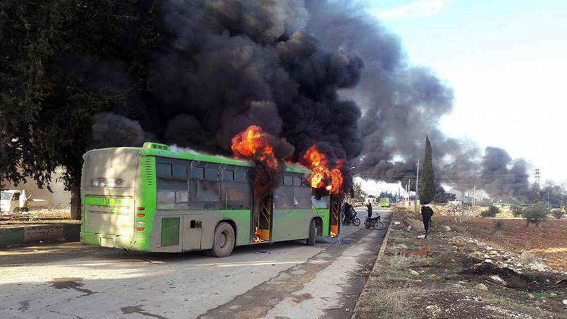 In this photo released by the Syrian official news agency SANA, smoke rises in green government buses, in Idlib province, Syria, Sunday, Dec. 18, 2016. Activists said, militants have burned at least five buses assigned to evacuate wounded and sick people from two villages in northern Syria. The incident could scuttle a wider deal that encompasses the evacuation of thousands of trapped rebel fighters and civilians from the last opposition foothold in east Aleppo. (SANA via AP)