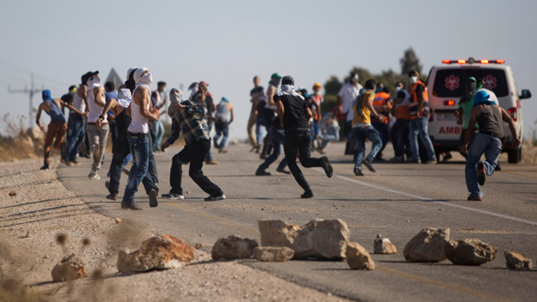 Aug. 8, 2015: Palestinians run for cover from tear gas fired by Israeli security forces during clashes that occurred after the funeral of Palestinian Saed Dawabsheh, 32, in the West Bank village of Duma near Nablus.