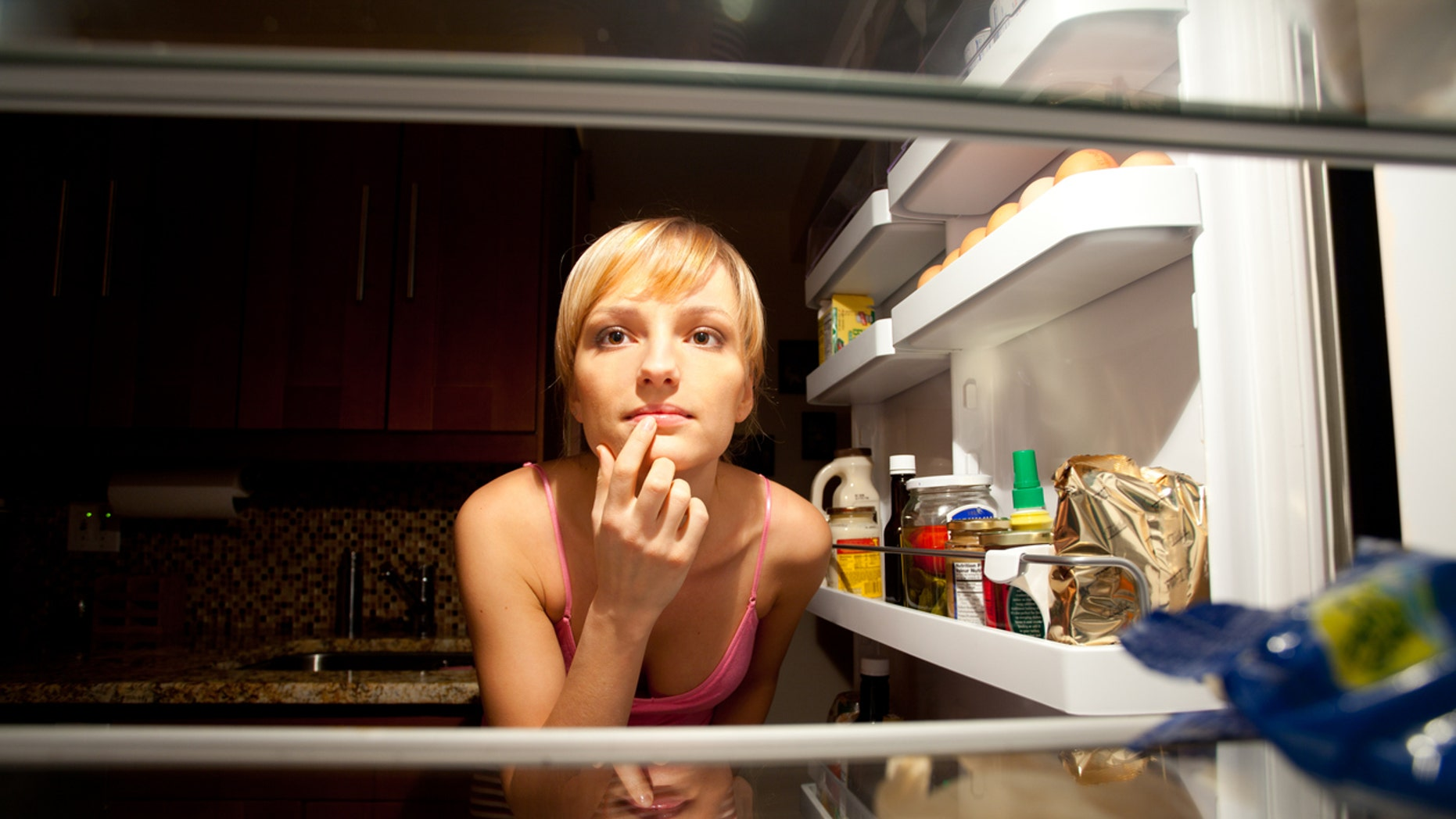 Woman thinking about her food choice inside refregirator in kitchen at night