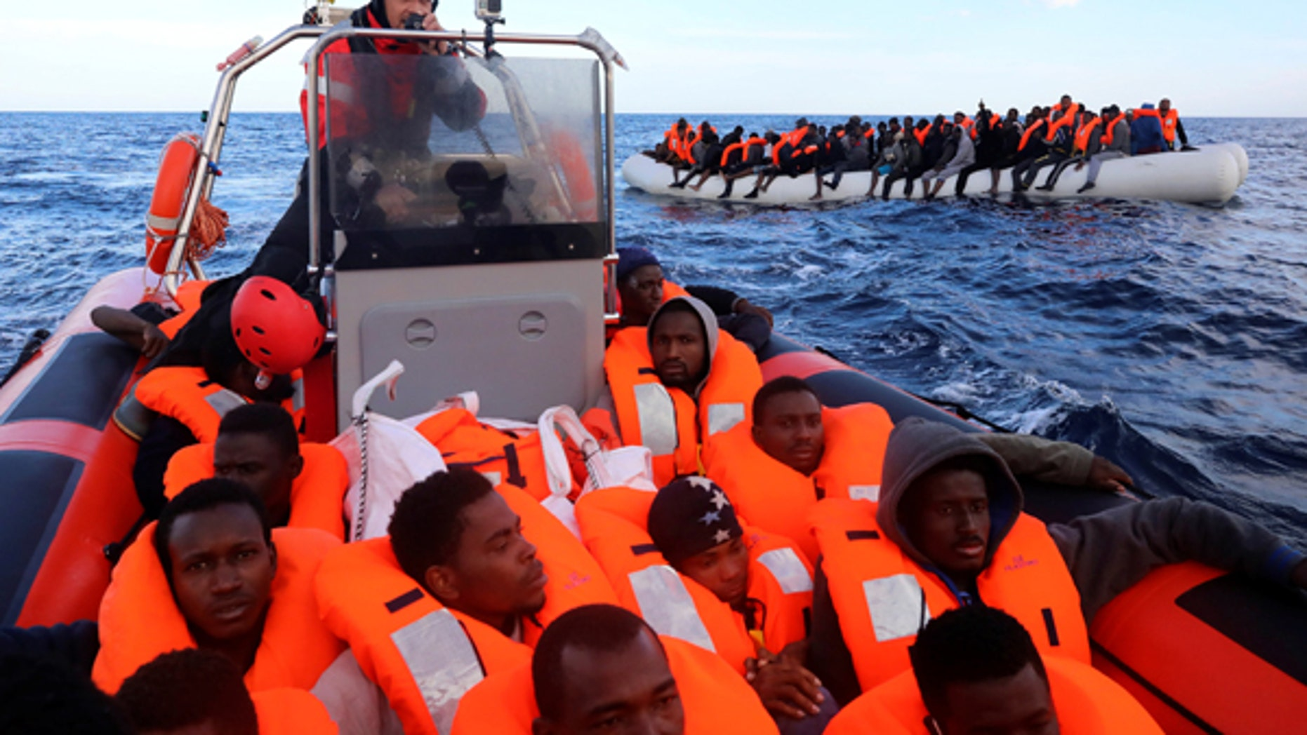 Sub-Saharan migrants are seen aboard an overcrowded raft as others are seen onboard a rescue boat, during a rescue operation by the Spanish NGO Proactiva Open Arms in the central Mediterranean Sea, 21 miles north of the coastal Libyan city of Sabratha.