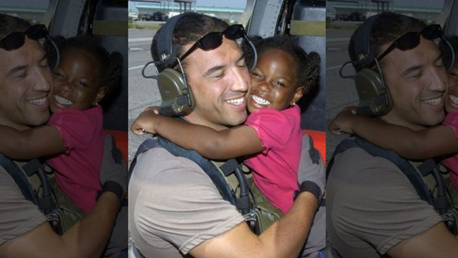 Air Force Reserve Master Sgt. Mike Maroney hugs 3-year-old he rescued in aftermath of Hurricane Katrina in 2005. (U.S. Air Force)