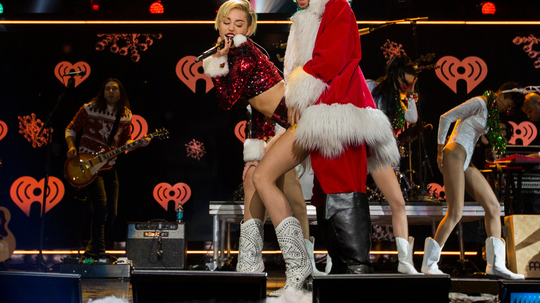 """December 13, 2013. Miley Cyrus """"twerks"""" a performer dressed as Santa Claus as she performs during the 2013 Z100 Jingle Ball in New York."""