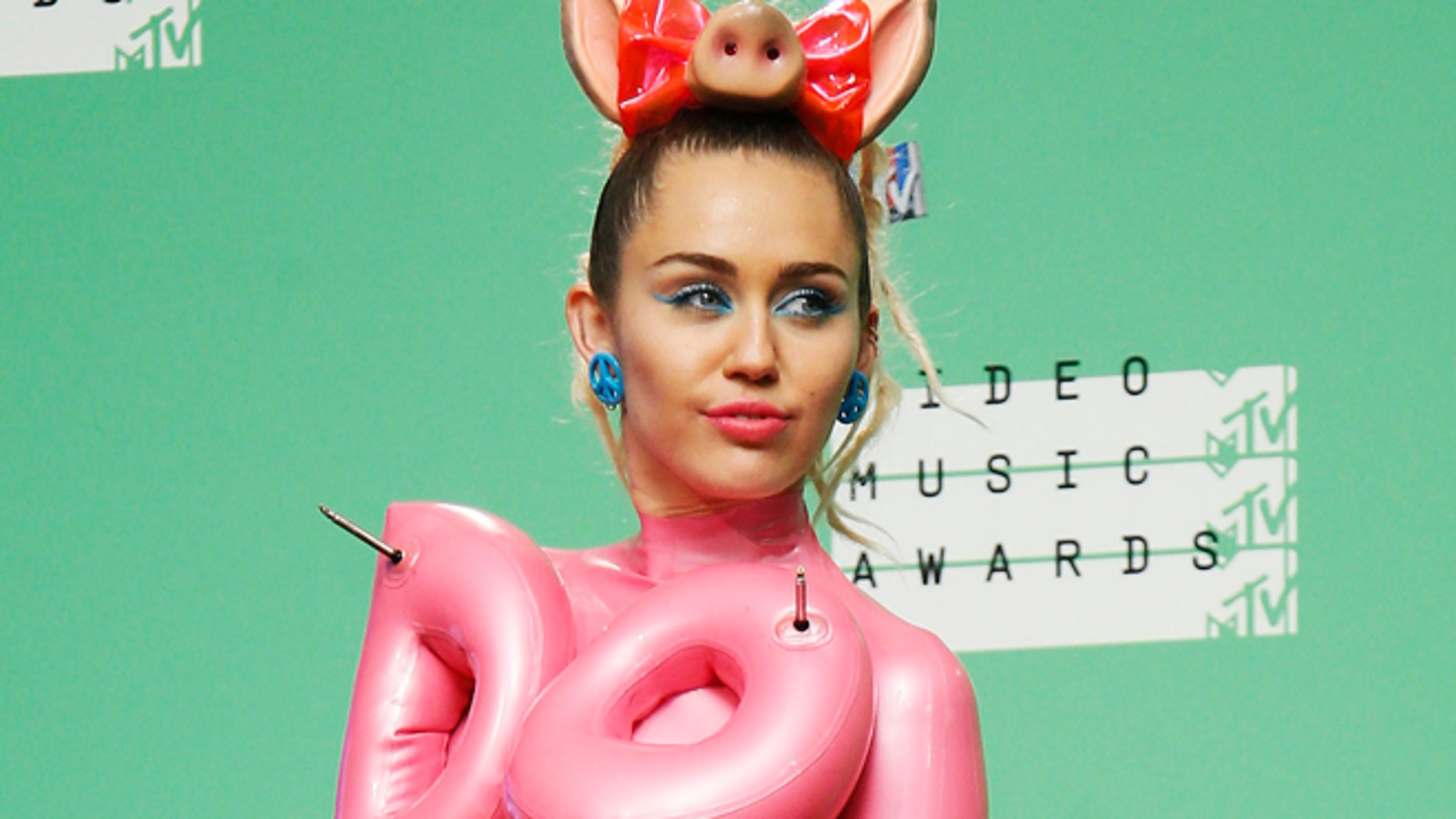 August 30, 2015. Miley Cyrus poses backstage after hosting the 2015 MTV Video Music Awards in Los Angeles, California.