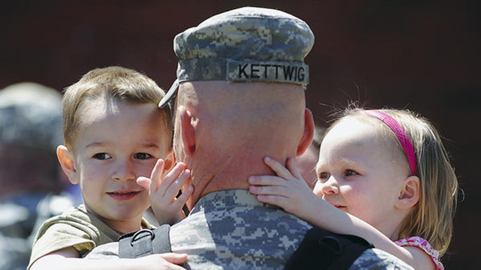 2011: Maj. Jason Kettwig of Milbank, S.D., greeted his children at a Sioux Falls, S.D., homecoming on May 3.  (Elisha Page/Argus Leader/AP)