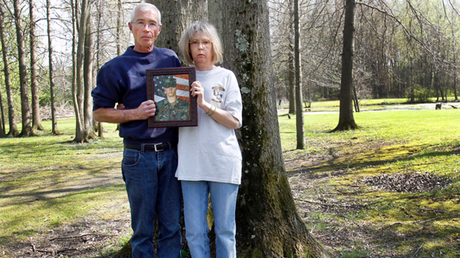 April 19, 2010: Matt and Cheryl Ecker hold a photo of their son, Army veteran Michael Ecker, in Champion, Ohio. On a warm summer afternoon in Champion, Michael Ecker, 25, an Iraq war veteran, called out to his father from a leafy spot in their backyard. Then, as the two stood just steps apart, Michael saluted, raised a gun to his head and pulled the trigger.