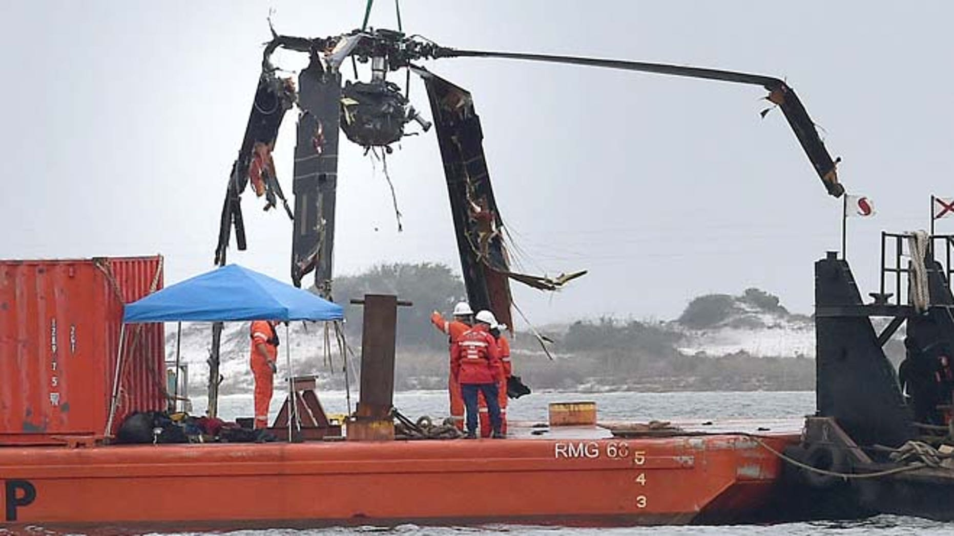 March 13, 2015: Crews lower a piece of a Black Hawk helicopter onto a barge in the Santa Rosa Sound near Pritchard Point in Navarre, Fla. (AP/Northwest Florida Daily News,  Nick Tomecek)