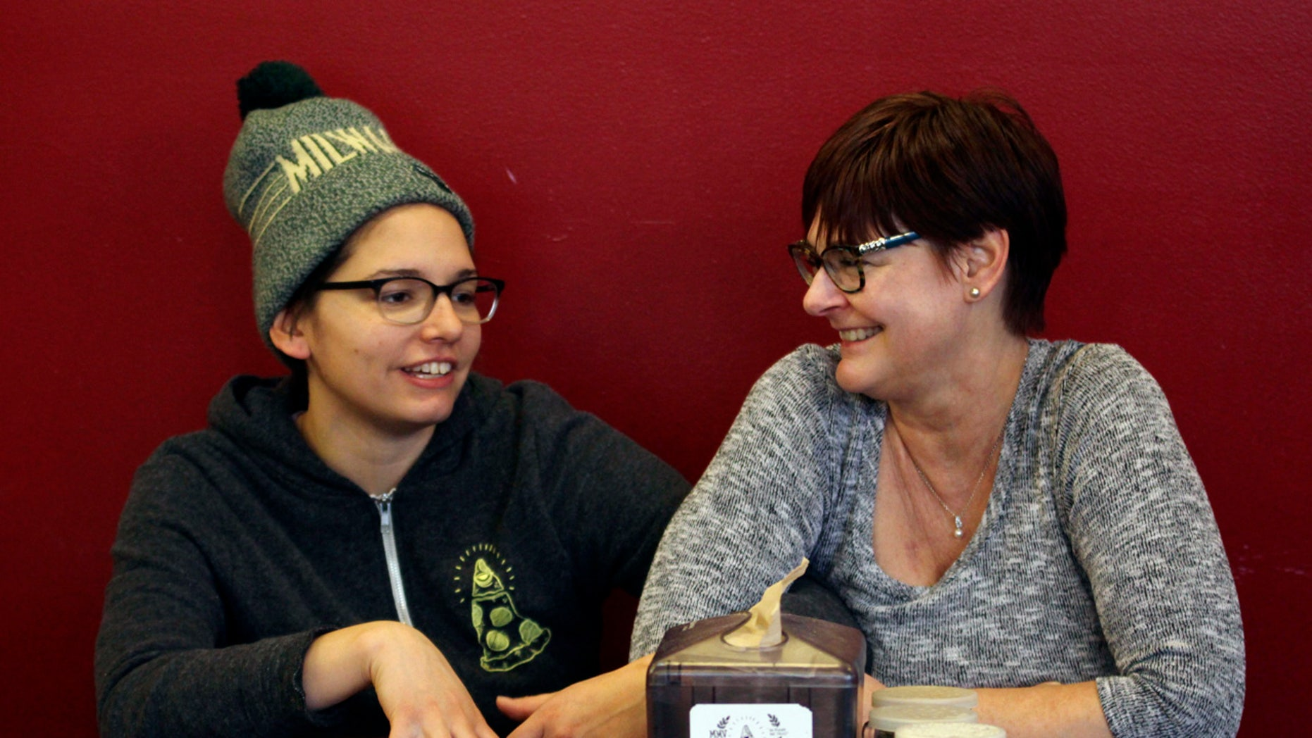In this Jan. 9, 2017, photo, Andrea Ledesma, left, talks with her mother, Cheryl Romanowski, at Classic Slice pizza restaurant, where Ledesma works, in Milwaukee.