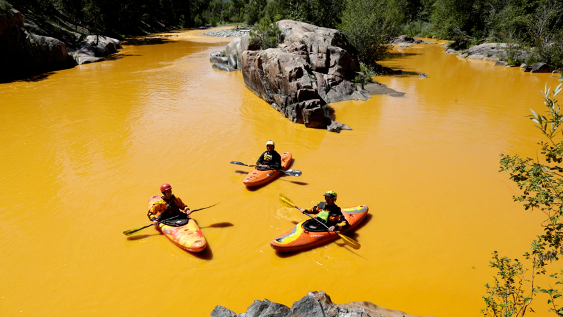 Aug. 6, 2015: People kayak in the Animas River near Durango, Colo., in water colored from a mine waste spill.