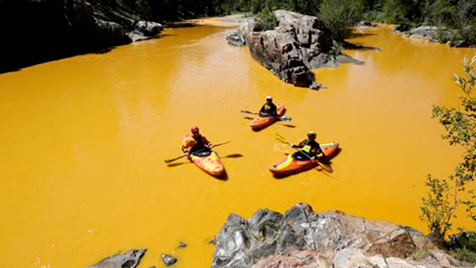 FILE - In this Aug. 6, 2015 file photo, people kayak in the Animas River near Durango, Colo., in water colored from a mine waste spill.  The federal government and Colorado have made little progress in remedying damages from the 2015 release of millions of gallons of wastewater from a southern Colorado mine, New Mexico's top prosecutor charged in a pair of scathing letters sent to officials on Friday, May 20, 2016.(Jerry McBride/The Durango Herald via AP, File) MANDATORY CREDIT