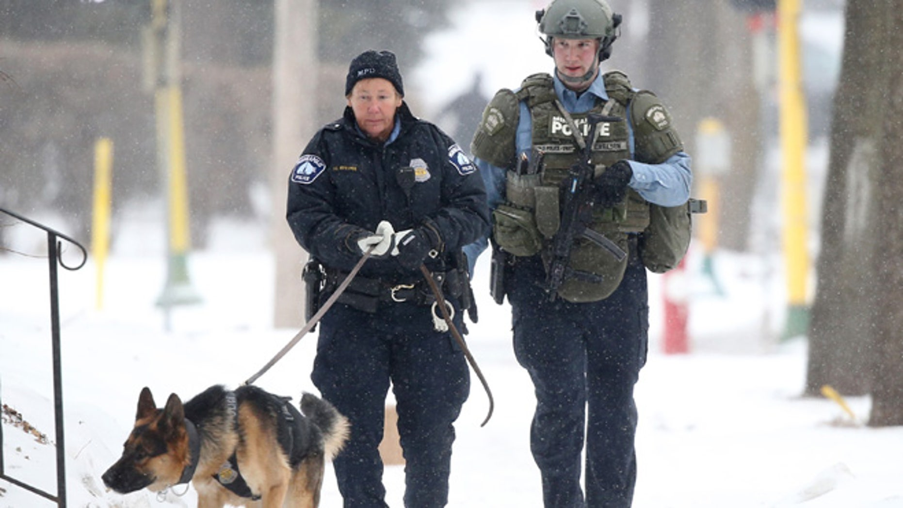 Feb. 21, 2015: An officer searches with a dog accompanied by a SWAT team member after a Minneapolis police officer was shot in Minneapolis.  (AP)
