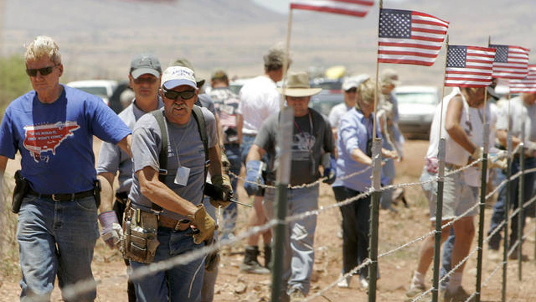 In this 2006 photo, Minuteman volunteers build a fence along the U.S./Mexican border near Palominas, Ariz., in the hope of reducing illegal immigration. Now, border militias in the state are gaining support after a bill that would have created a civilian border group failed in the state Legislature.