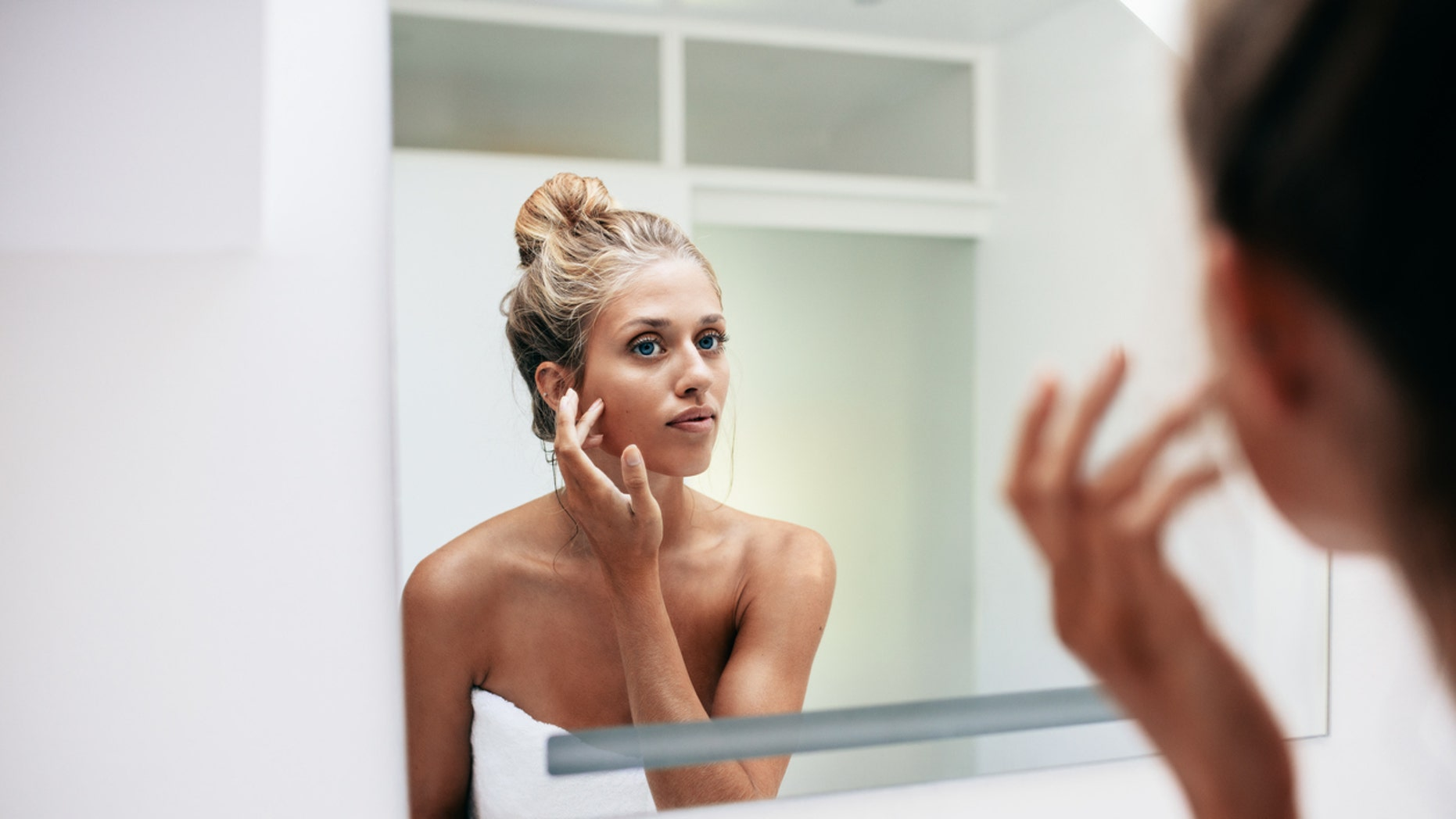 Beautiful young woman standing in the bathroom. Female looking into the mirror and touching her face skin.