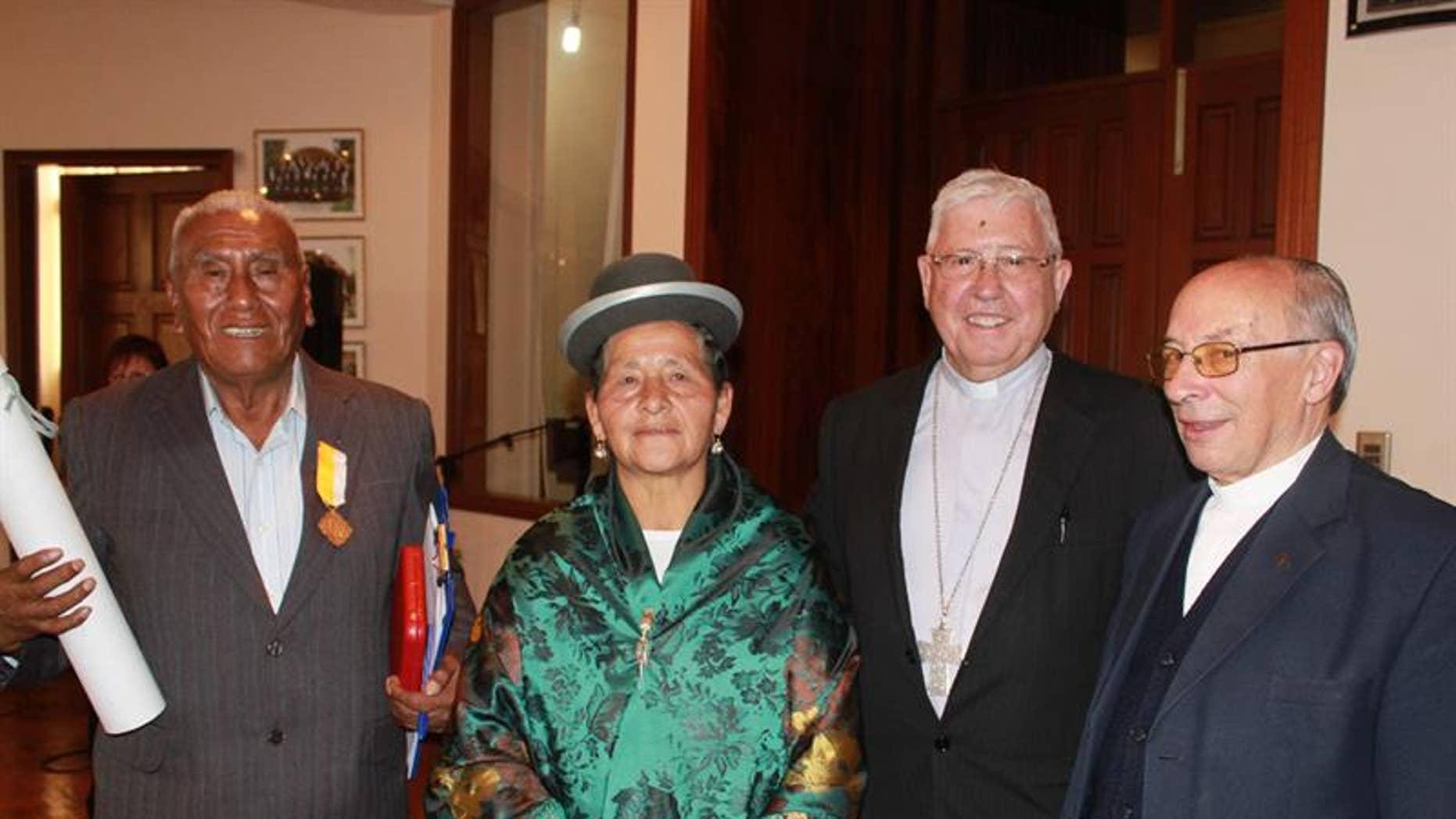 Spanish Jesuit Luis Palomera (R) and Sucre Department Arzbishop Jesus Juarez pose with Vicente Quispe Chura and his wife Francisca Carlo de Quispe.