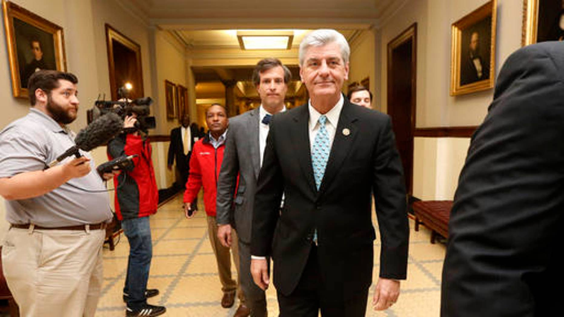 FILE -- April 1, 2016: Republican Gov. Phil Bryant, right, walks past reporters on his way to a meeting of a youth jobs program board, at the Capitol in Jackson, Miss.
