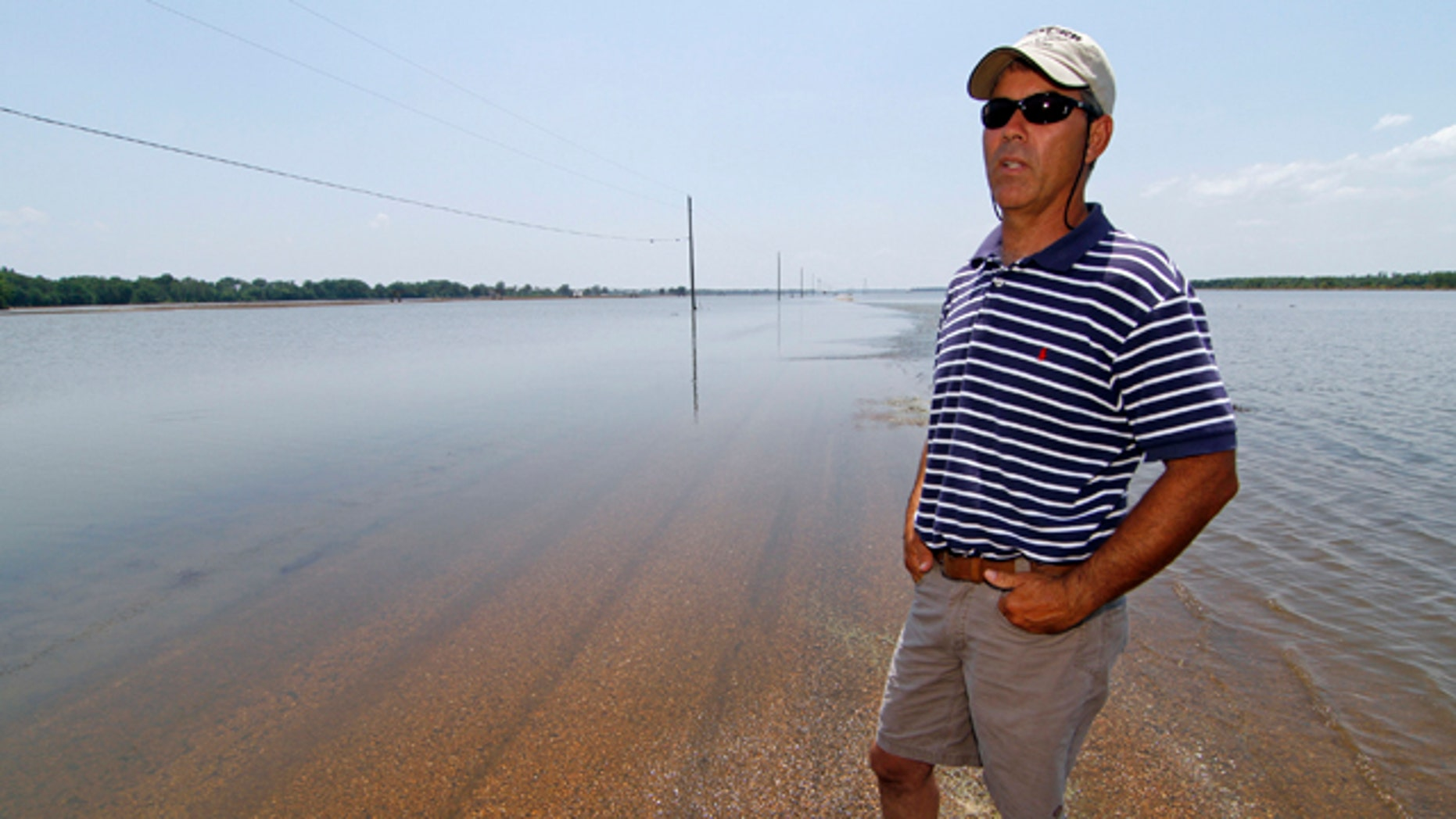 June 1: Farmer Brett Robinson stands on the road between his flooded farm fields near his house outside of Yazoo City, Miss.