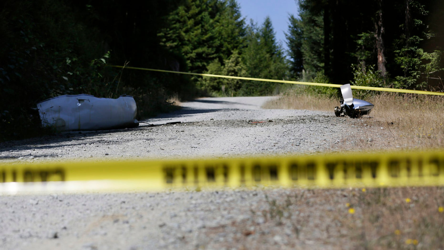 July 29, 2016: An engine nose cone with a bent propeller blade and other wreckage from a medical transport plane that crashed are shown on a road east of Crannell, Calif.