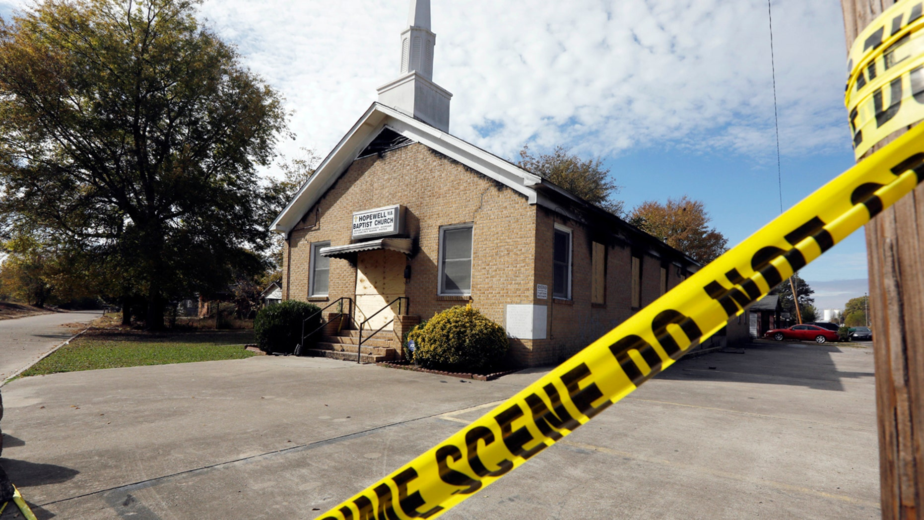 """Crime scene tape outlines the perimeter of the Hopewell Missionary Baptist Church in Greenville, Miss., on Tuesday, Nov. 22, 2016, after the church was burned and spray-painted with """"Vote Trump,"""" three weeks ago. T"""