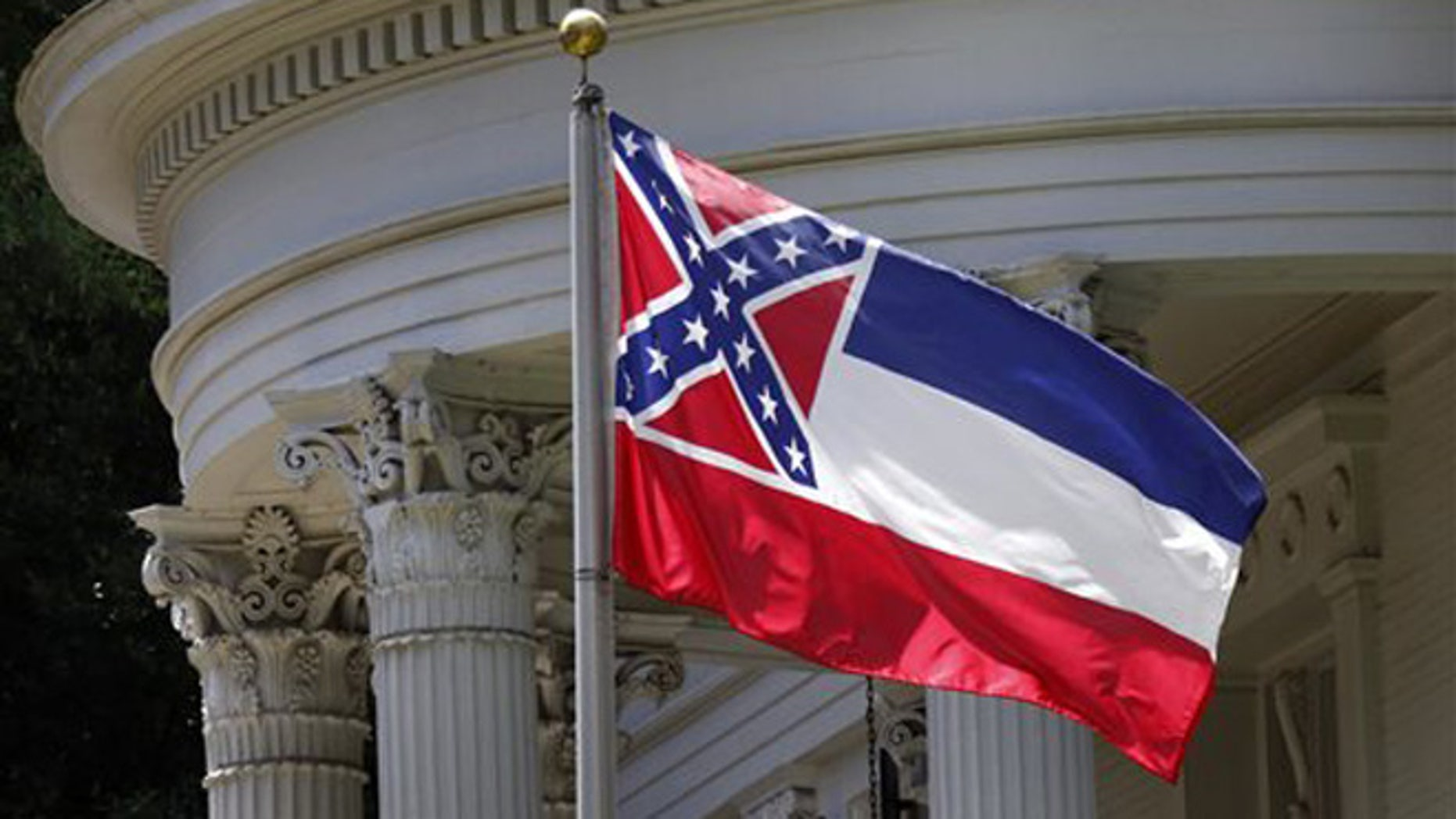 In this photo, the Mississippi state flag is unfurled against the front of the Governor's Mansion in Jackson, Miss.