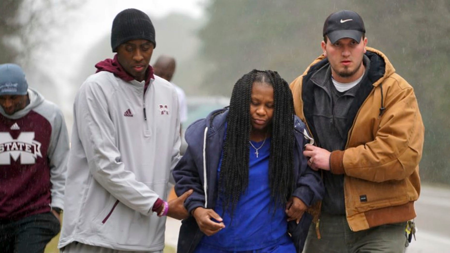 In this image taken Friday, Jan. 6, 2016, and released by Mississippi State Athletics, Mississippi State trainer Ryan Dotson, left, and an unidentified man aid a motorist who's car flipped over in front of the team bus in Mississippi, as they were heading to LSU for an NCAA college basketball game. (Drew Walker/Mississippi State Athletics via AP)