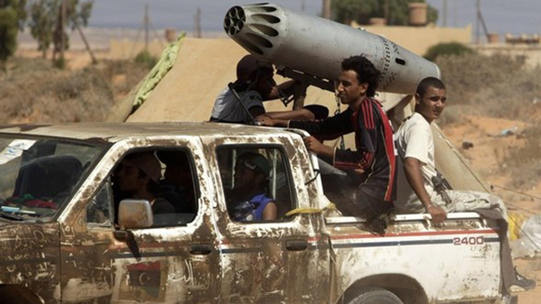 Sept. 14: Anti-Qaddafi fighters drive with a converted missile launcher from an aircraft near a check point.