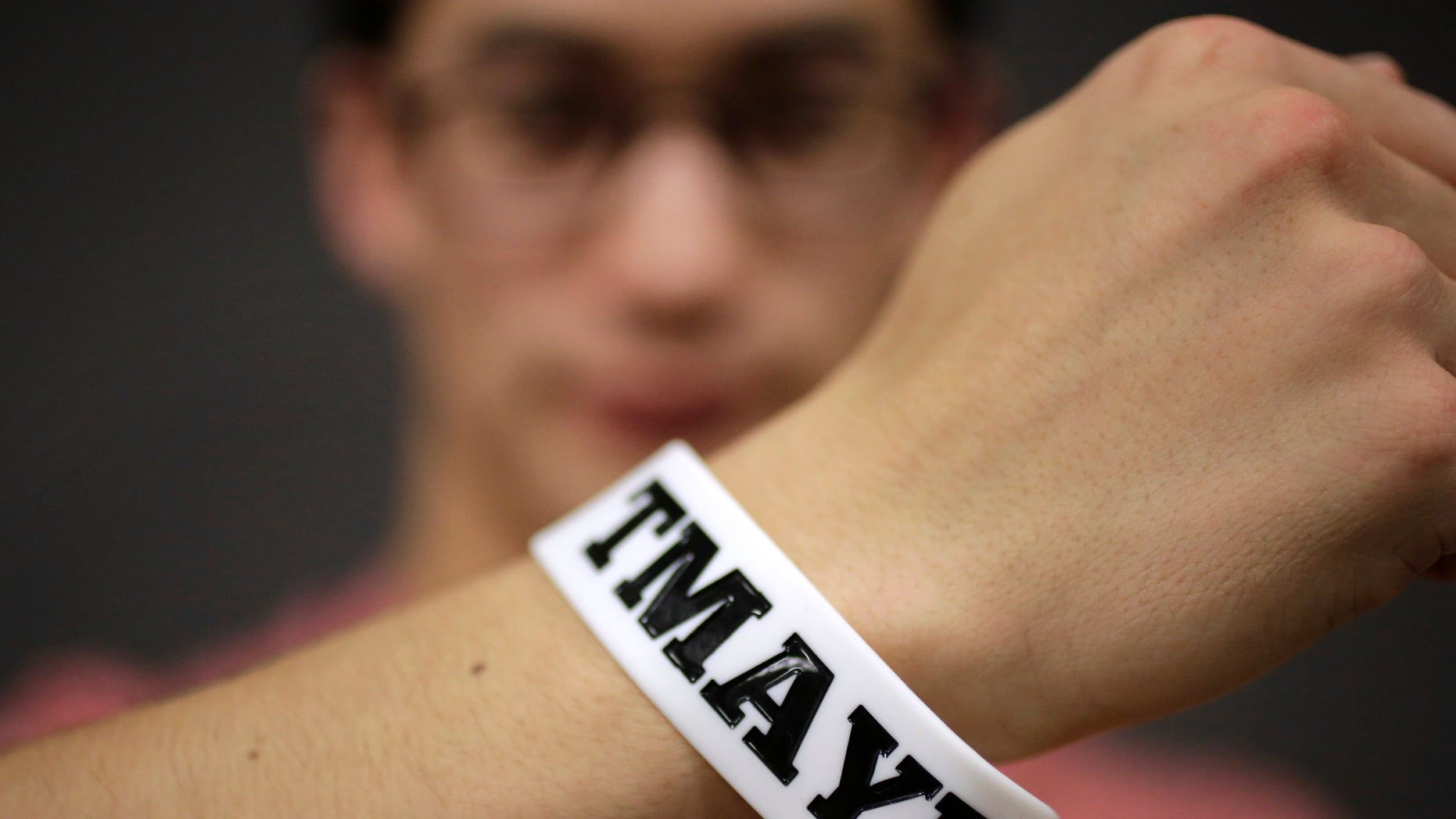 "In this Monday, Feb. 1, 2016 photo, Massachusetts Institute of Technology student Andy Trattner, of Portland, Ore., displays a wrist band that features the acronym TMAYD for ""Tell Me About Your Day,"" a campaign to encourage students to talk to one another in an effort to defuse to the stress of campus life before it leads to a crisis. There were several campus suicides last year. MIT officials recently set aside thousands of dollars for grants to help support campus projects dealing with mental health. (AP Photo/Steven Senne)"