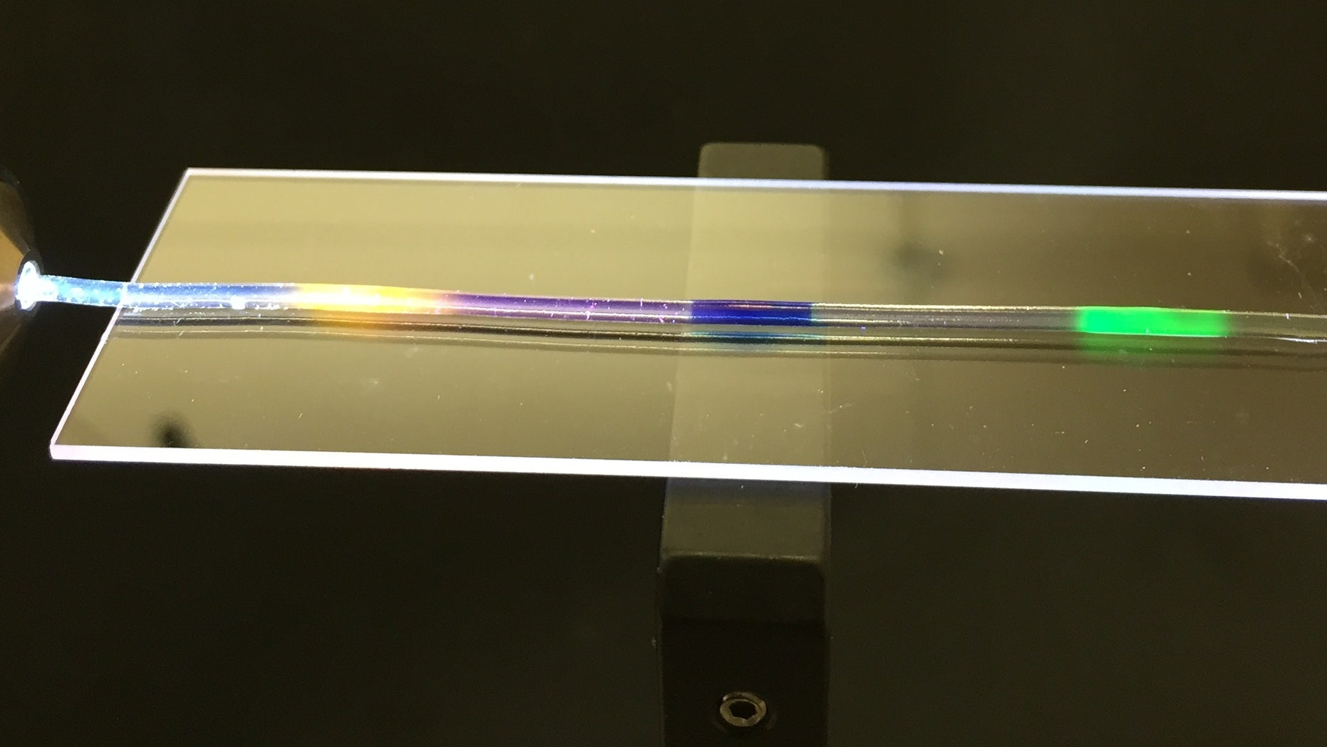 MIT researchers have developed a stretchy optical fiber in which they have injected multiple organic dyes (yellow, blue, and green regions). In addition to lighting up, the dyes act as a strain sensor, enabling researchers to quantify where and by how much a fiber has been stretched. (Courtesy of the researchers)