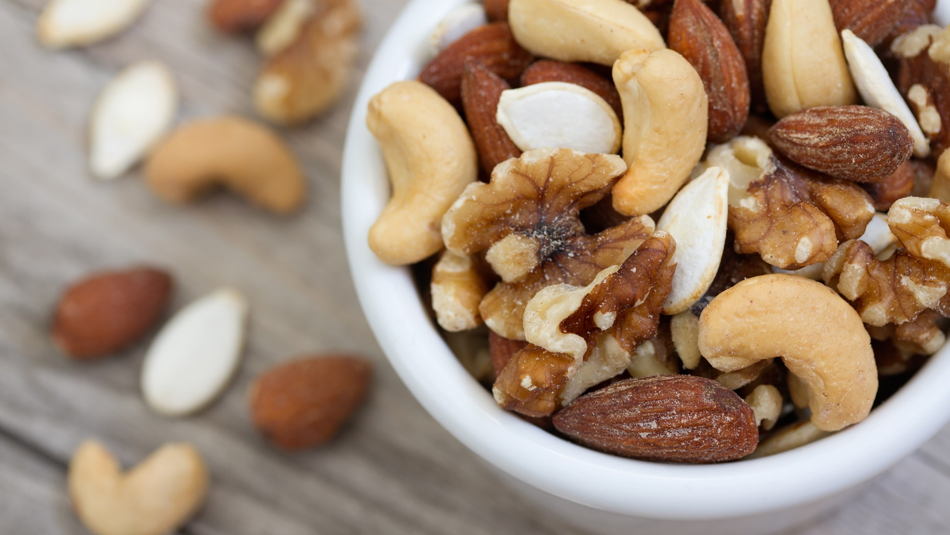 Bowl of mixed nuts on rustic wooden table in natural light.