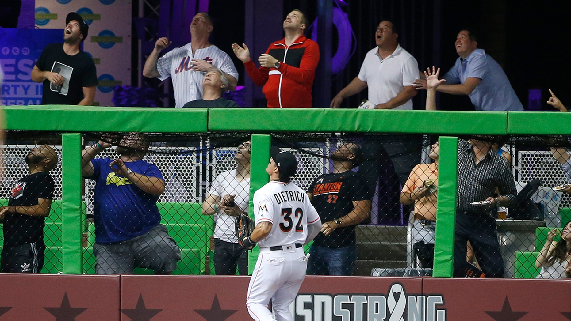 Miami Marlins left fielder Derek Dietrich (32) and fans look on as a ball hit by New York Mets' Asdrubal Cabrera goes over the wall for a home run during the fourth inning.