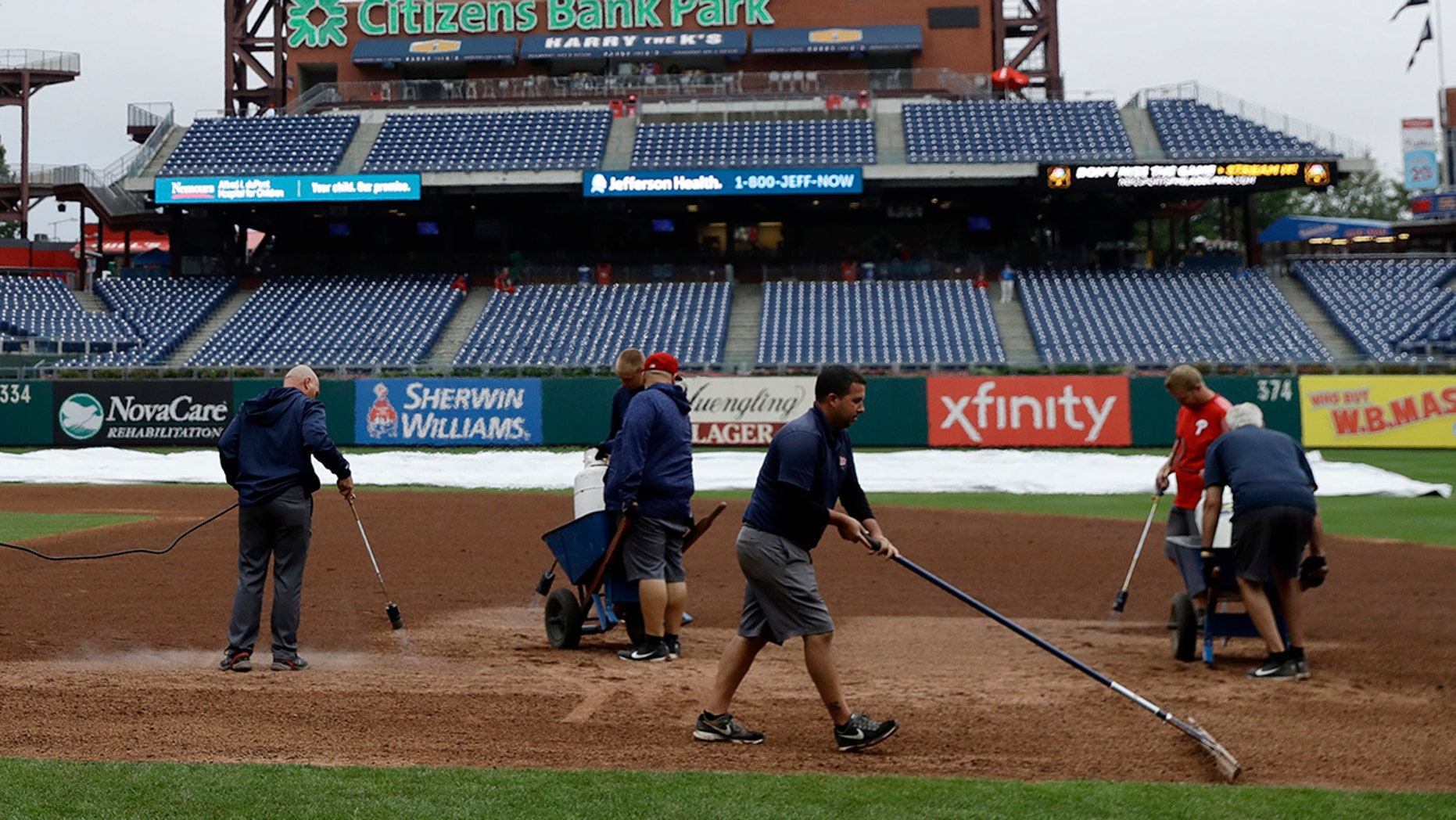 Grounds crew members attempted to dry the Phillies' infield with blow torches.