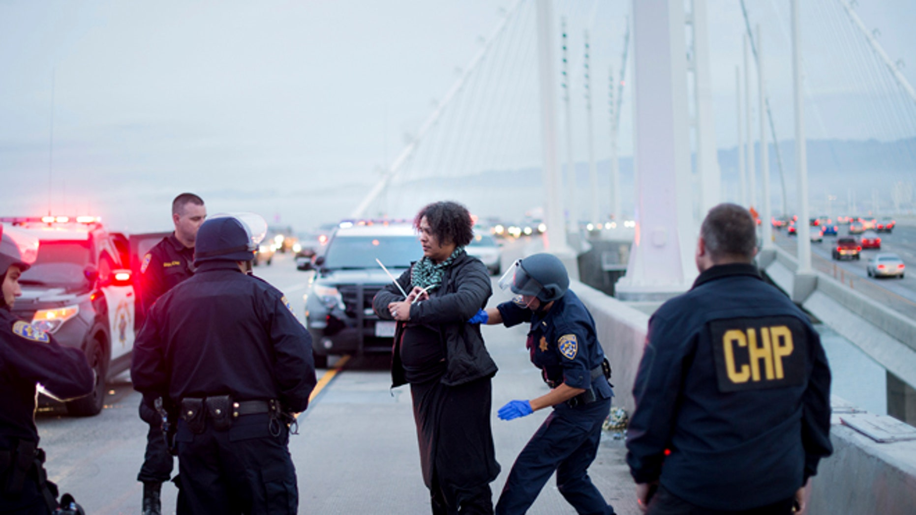 A California Highway Patrol officer detains a protester on the San Francisco-Oakland Bay Bridge, Monday, Jan. 18, 2016, in San Francisco. A group of protesters from the group Black Lives Matter caused the shutdown of one side of the bridge in a police-brutality protest tied to the Rev. Martin Luther King Jr. holiday. (AP Photo/Noah Berger)