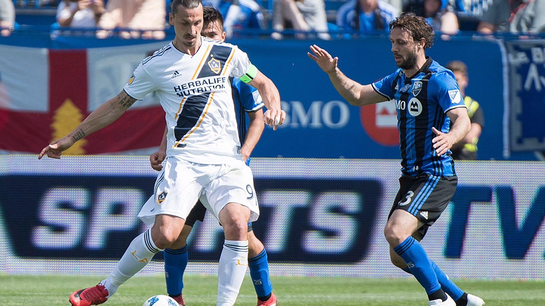 Montreal Impact's Marco Donadel moves in on Los Angeles Galaxy's Zlatan Ibrahimovic, left, during the first half an MLS soccer match in Montreal.