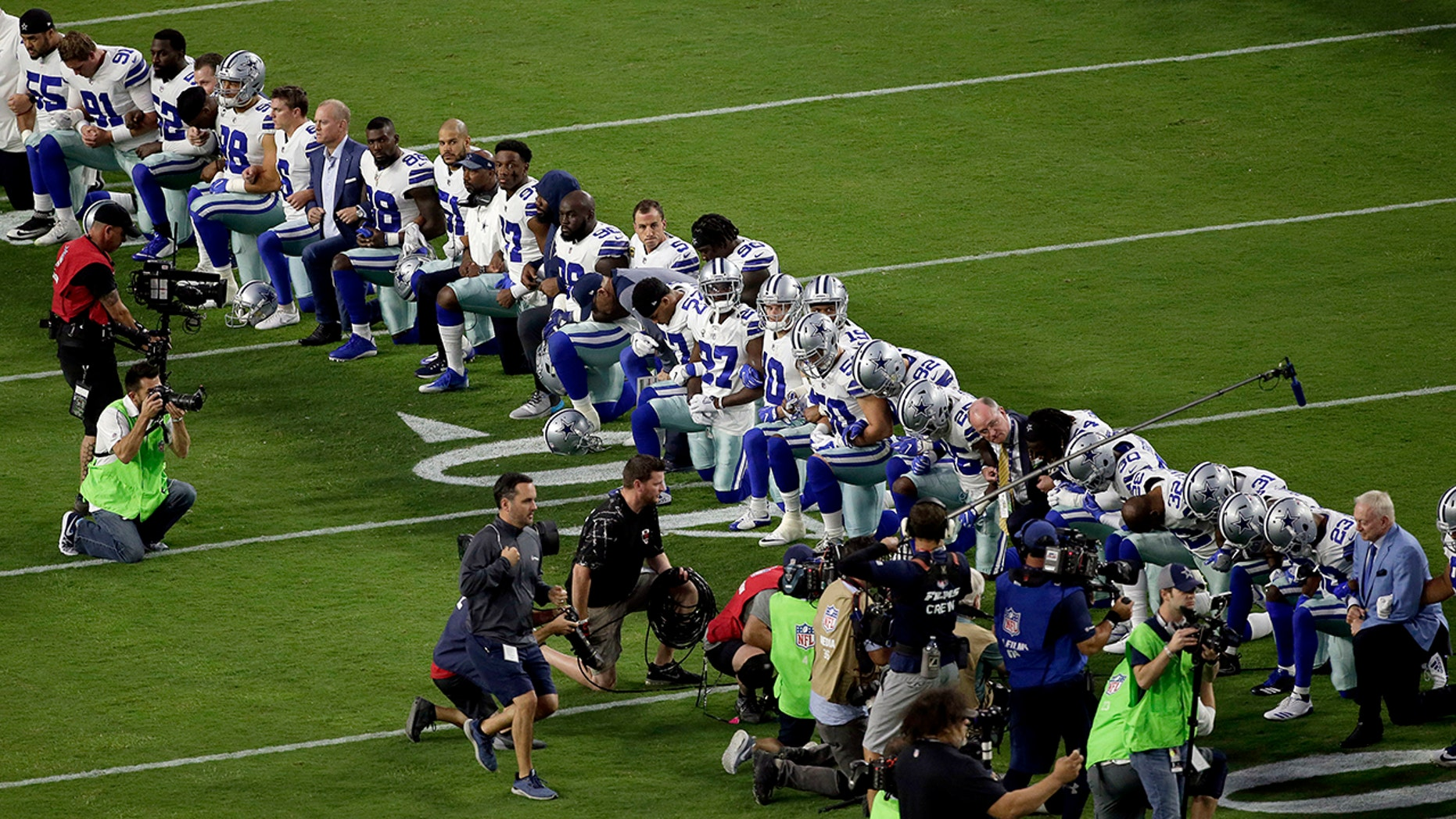 The Dallas Cowboys, led by owner Jerry Jones, far right, take a knee prior to the national anthem prior to an NFL football game against the Arizona Cardinals, Monday, Sept. 25, 2017, in Glendale, Ariz.