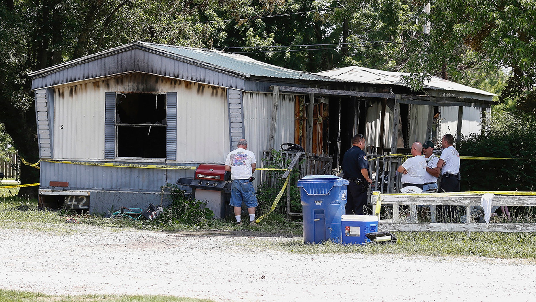 Investigators look over the remains of a deadly fire, in Lebanon, Mo., June 6, 2018.