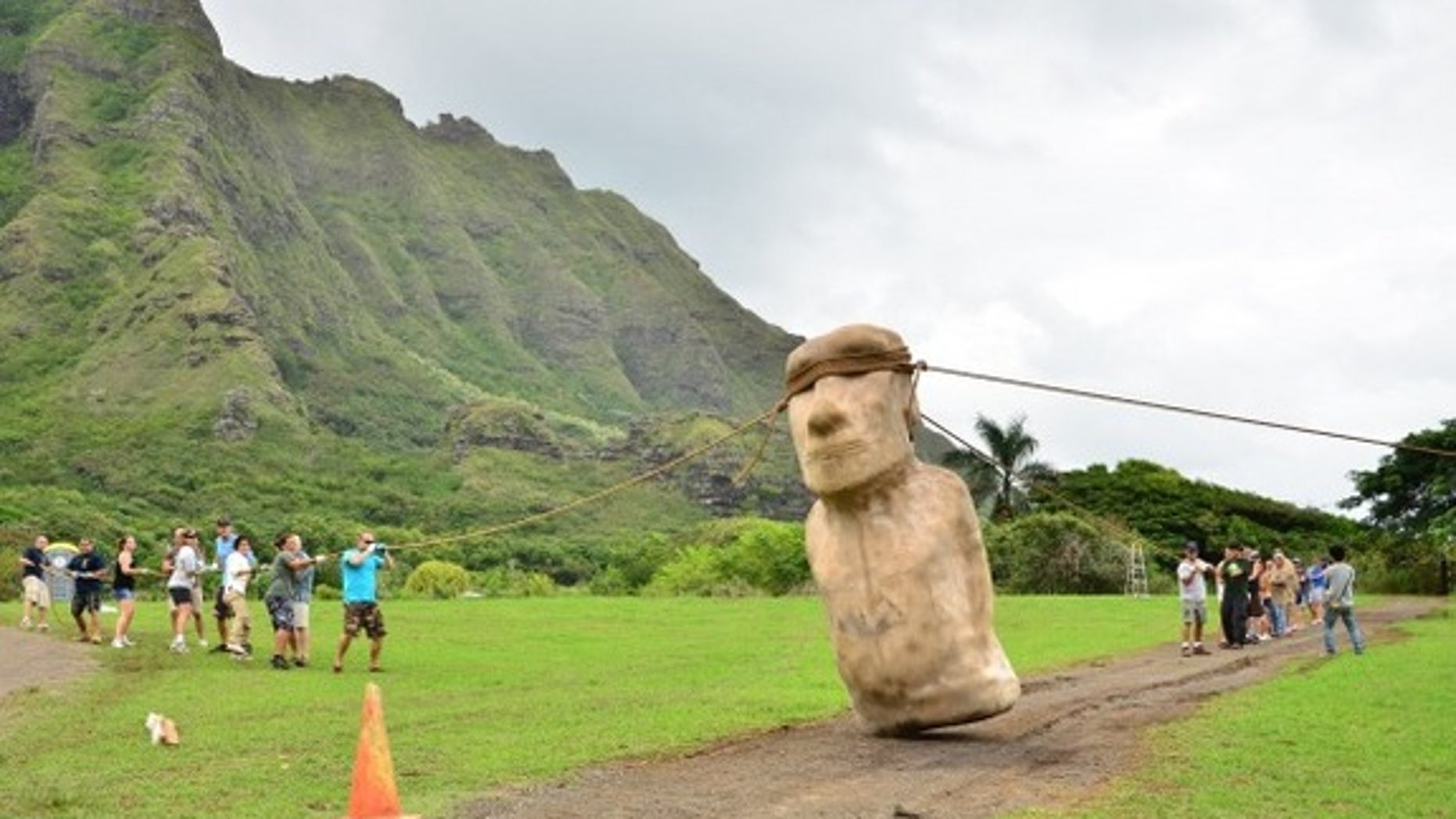 An Easter Island statue being walked into place
