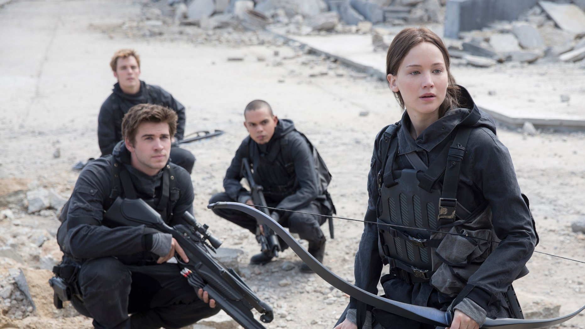 """Liam Hemsworth, left, as Gale Hawthorne, Sam Clafin, back left, as Finnick Odair, Evan Ross, back right, as Messalia, and Jennifer Lawrence, right, as Katniss Everdeen, in the film, """"The Hunger Games: Mockingjay - Part 2."""""""