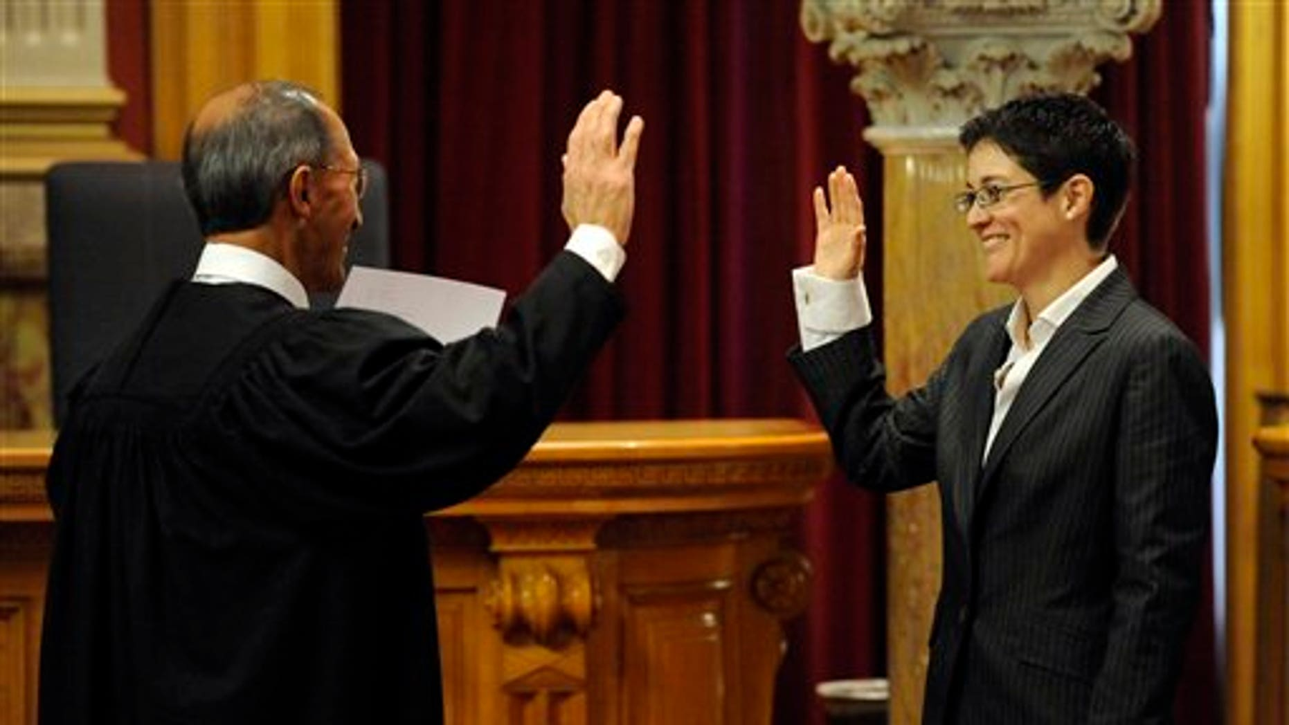 Monica Marquez is sworn in as a new State supreme court justice by her father, senior judge Jose Marquez, at the State Capitol Friday, Dec. 10, 2010, in Denver. Marquez replaced retired Chief Justice Mary Mullarkey.  (AP Photo/Jack Dempsey)