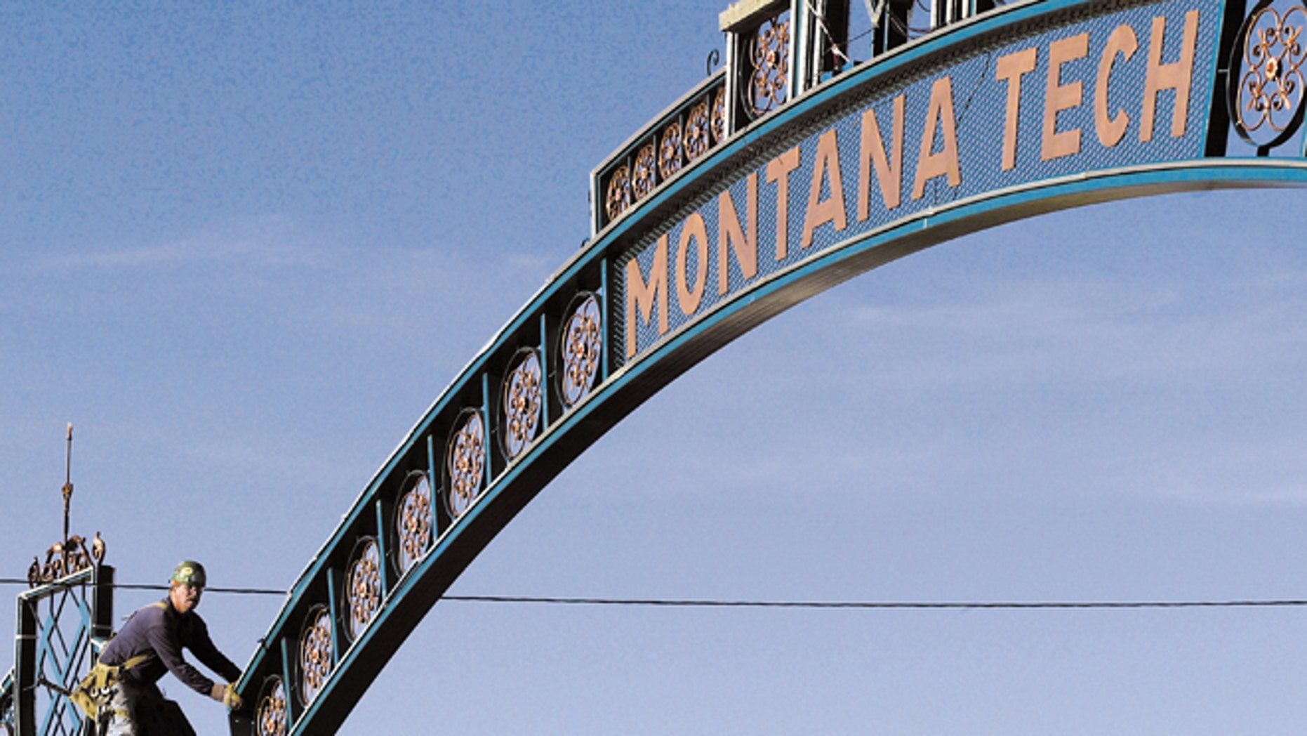 In this Aug. 26, 2003, file photo, Butch Schelin guides the new Montana Tech archway into place above Park Street in Butte, Mont. Montana Tech has expelled 15 summer school students for cheating.