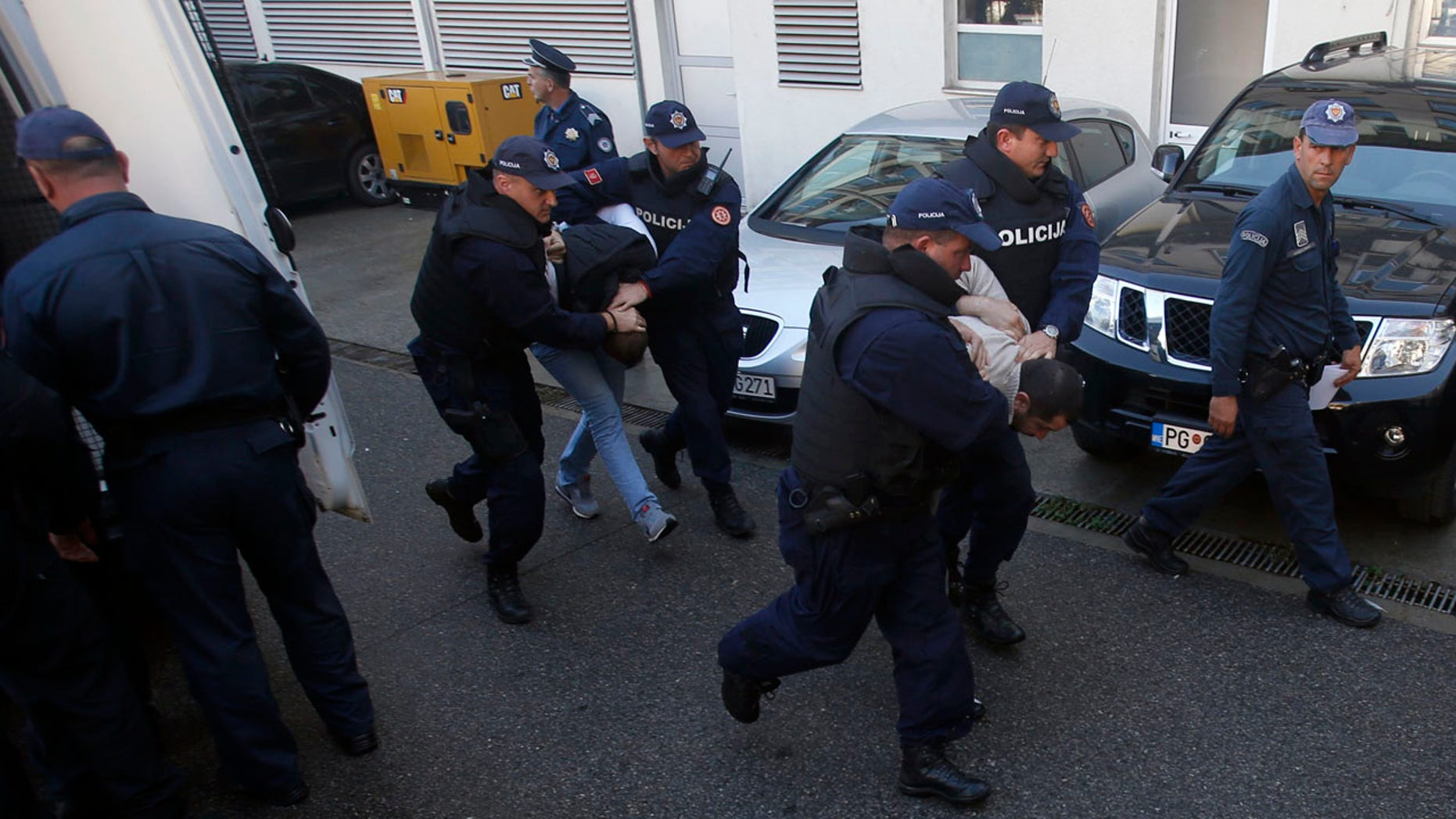 Oct. 16, 2016: Montenegrin police officers escort people suspected of planning armed attacks after the parliamentary vote in Podgorica, Montenegro.