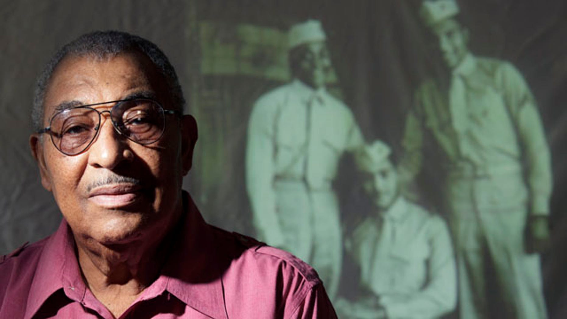 Oct. 5, 2011: Carrel Reavis poses for a portrait in front of an image of him, far right, with two friends taken in the late 1940s in San Diego. Nearly 70 years after the Marine Corps, the last military branch to racially integrate, accepted segregated black units, the Marine Corps' top general had sought to honor the history of the Montford Point Marines.