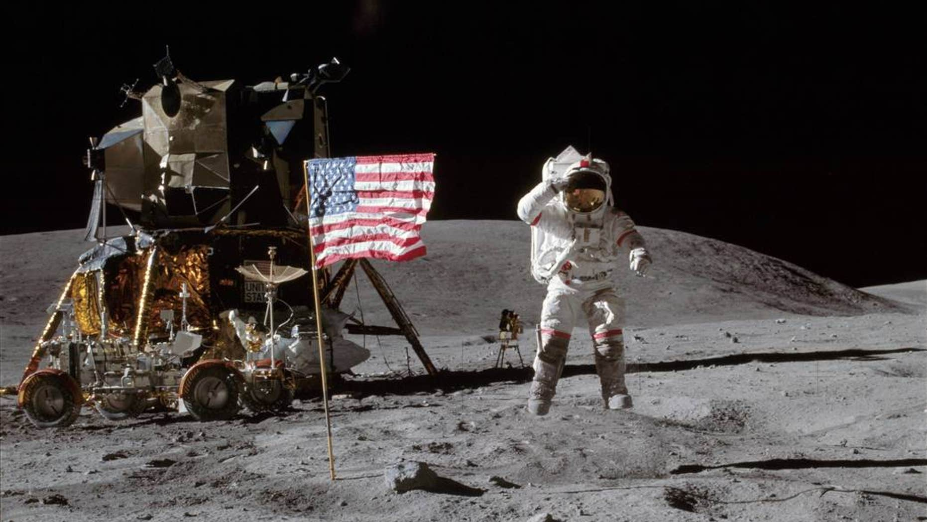 NASA astronaut John W. Young, commander of the Apollo 16 lunar landing mission, is pictured here with the American flag on the surface of the moon. The low-gravity environment allowed him to leap from the lunar surface.