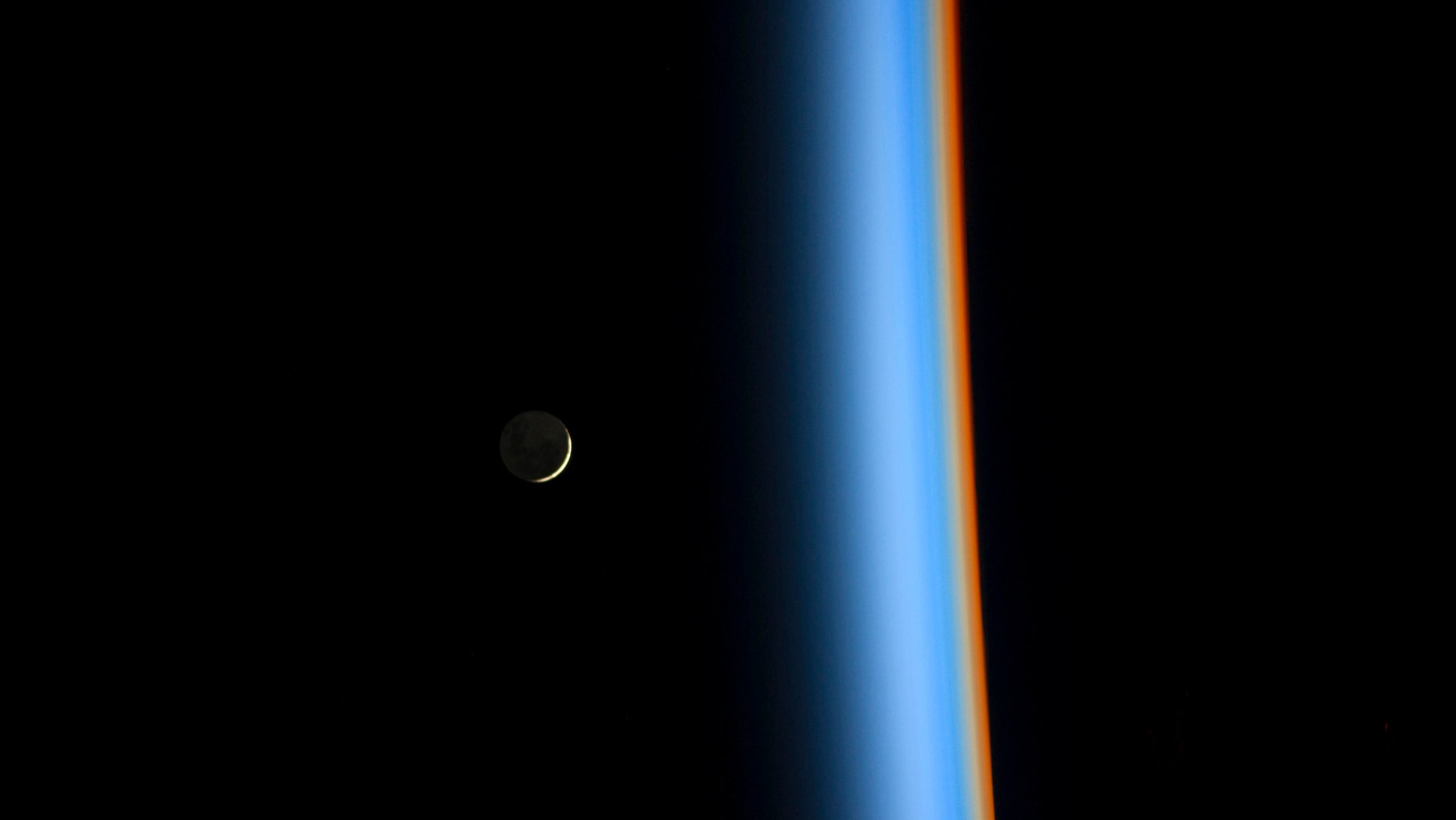 A crescent moon rises over the cusp of the Earth's atmosphere.