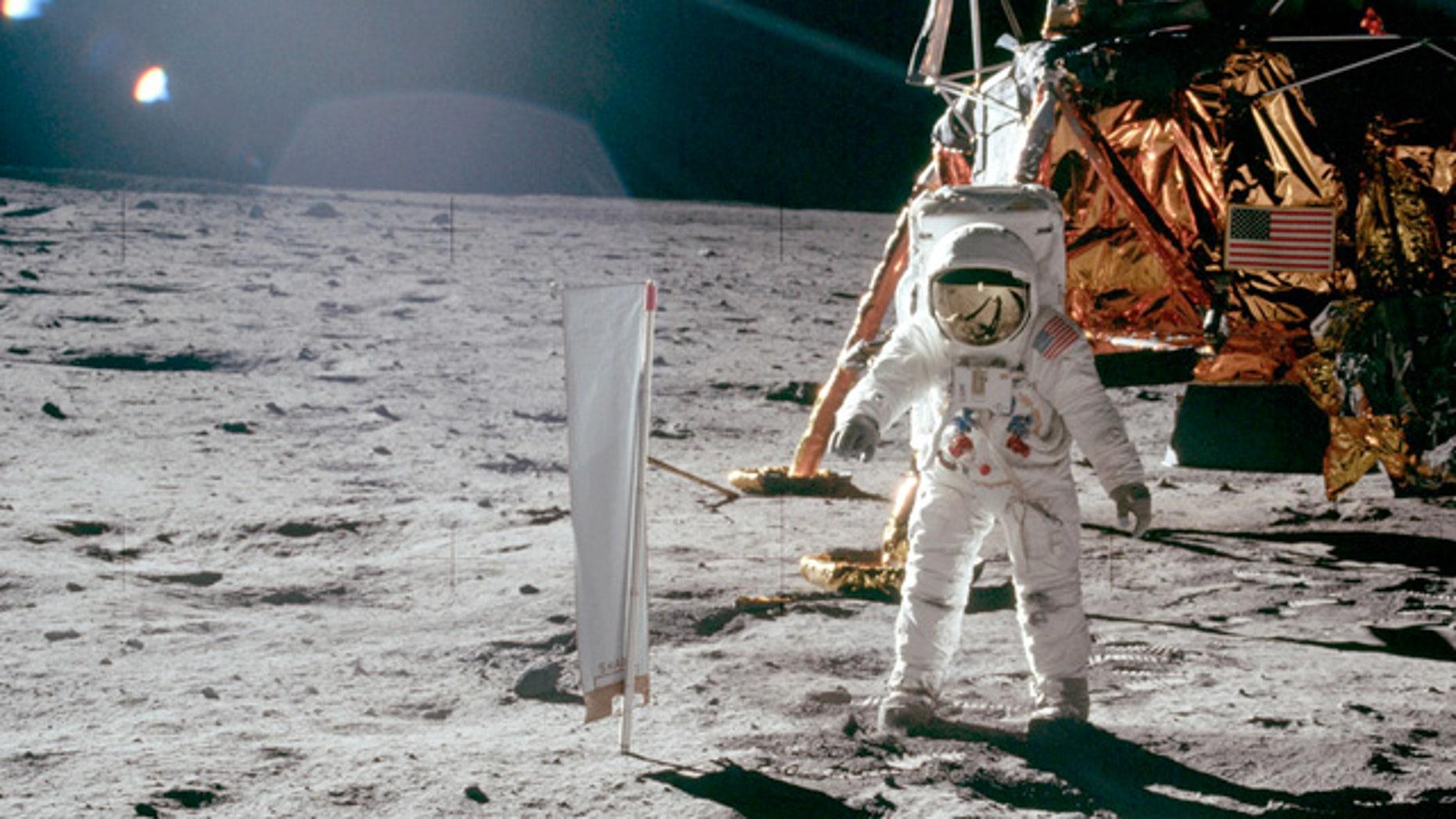 Buzz Aldrin stands on lunar surface in front Lunar Landing Module during Apollo 11's lunar mission.