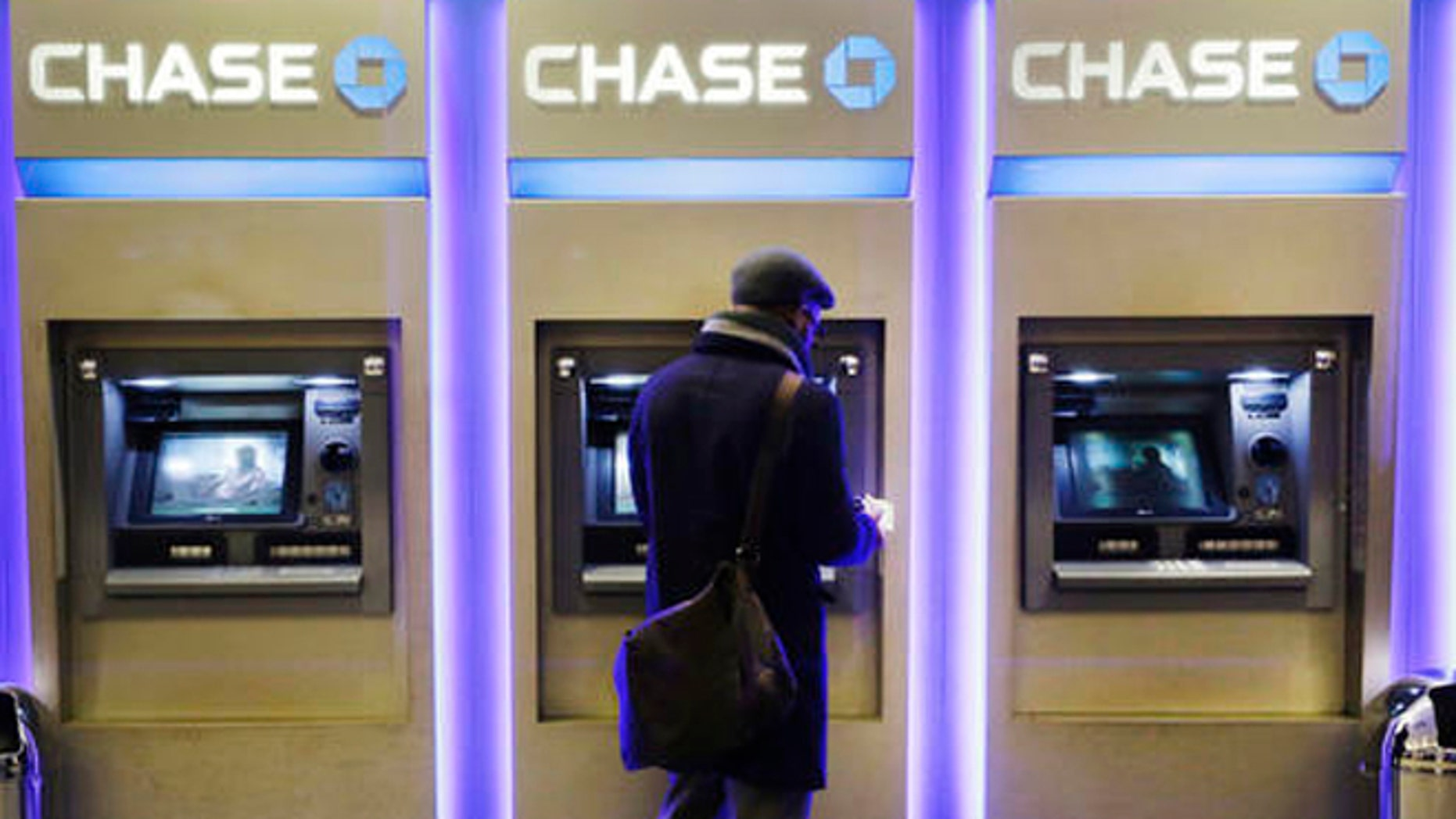 FILE - In this Wednesday, Jan. 14, 2015, file photo, a customer uses an ATM at a branch of Chase Bank, in New York. Fewer Americans are without access to a checking or savings account, according to a survey released Thursday, Oct. 20, 2016, by federal regulators, a sign that the improving economy is helping lift the nation's poorest households. (AP Photo/Mark Lennihan, File)