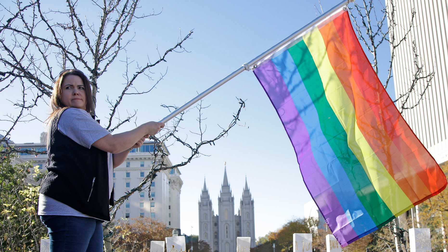 Sandy Newcomb poses with a rainbow flag as Mormons gather for a mass resignation from the Church of Jesus Christ of Latter-day Saints.