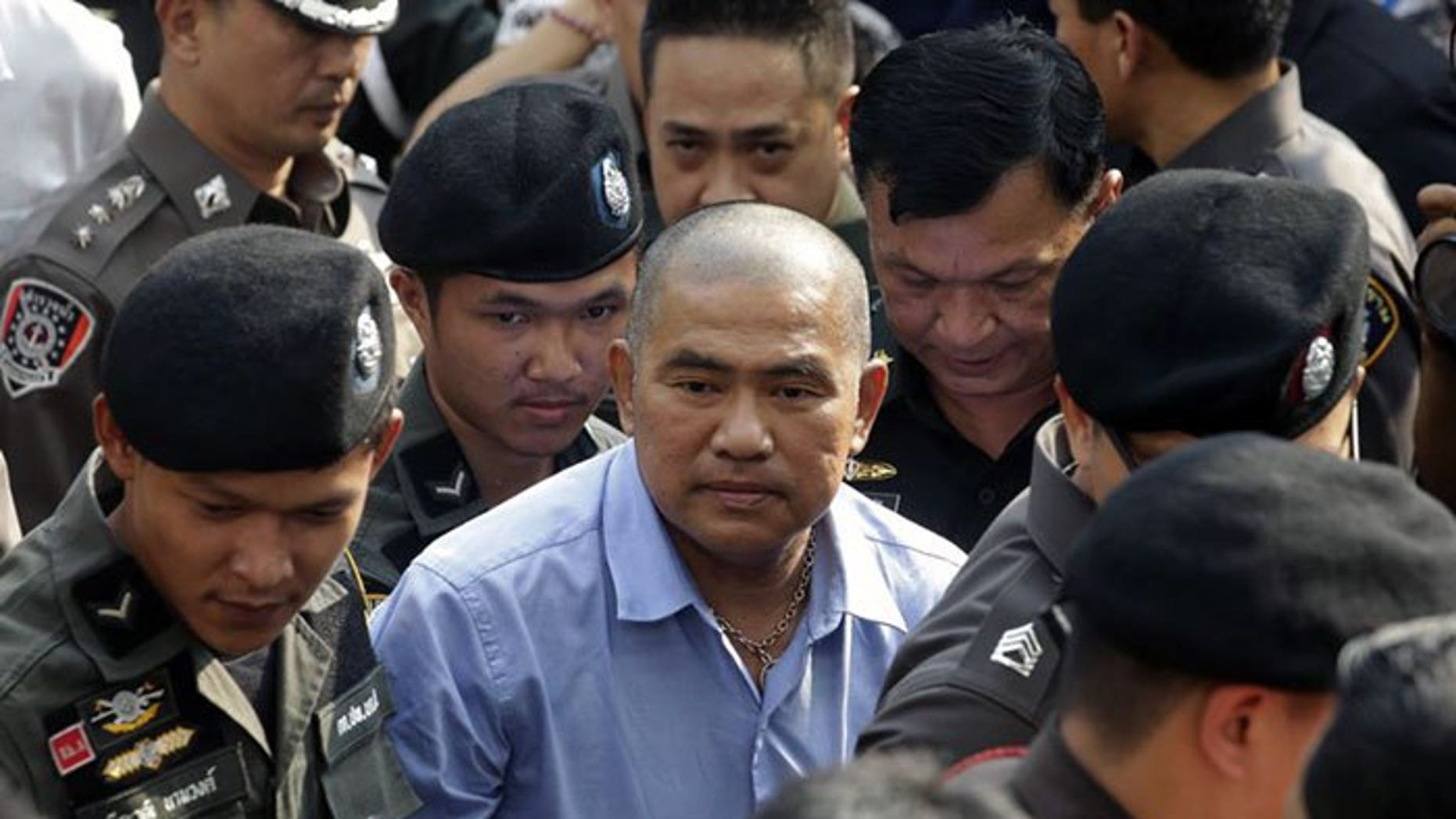 """The fortune-teller known as """"Mor Yong,"""" in blue shirt, arriving at a Thai military court in October."""