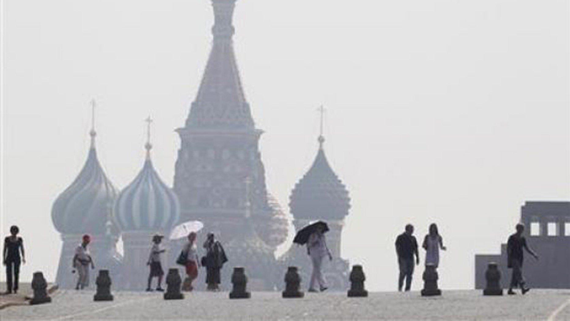 People walk along Red Square, with St. Basil's Cathedral seen through heavy smog caused by peat fires in out-of-city forests, in Moscow, July 26, 2010.