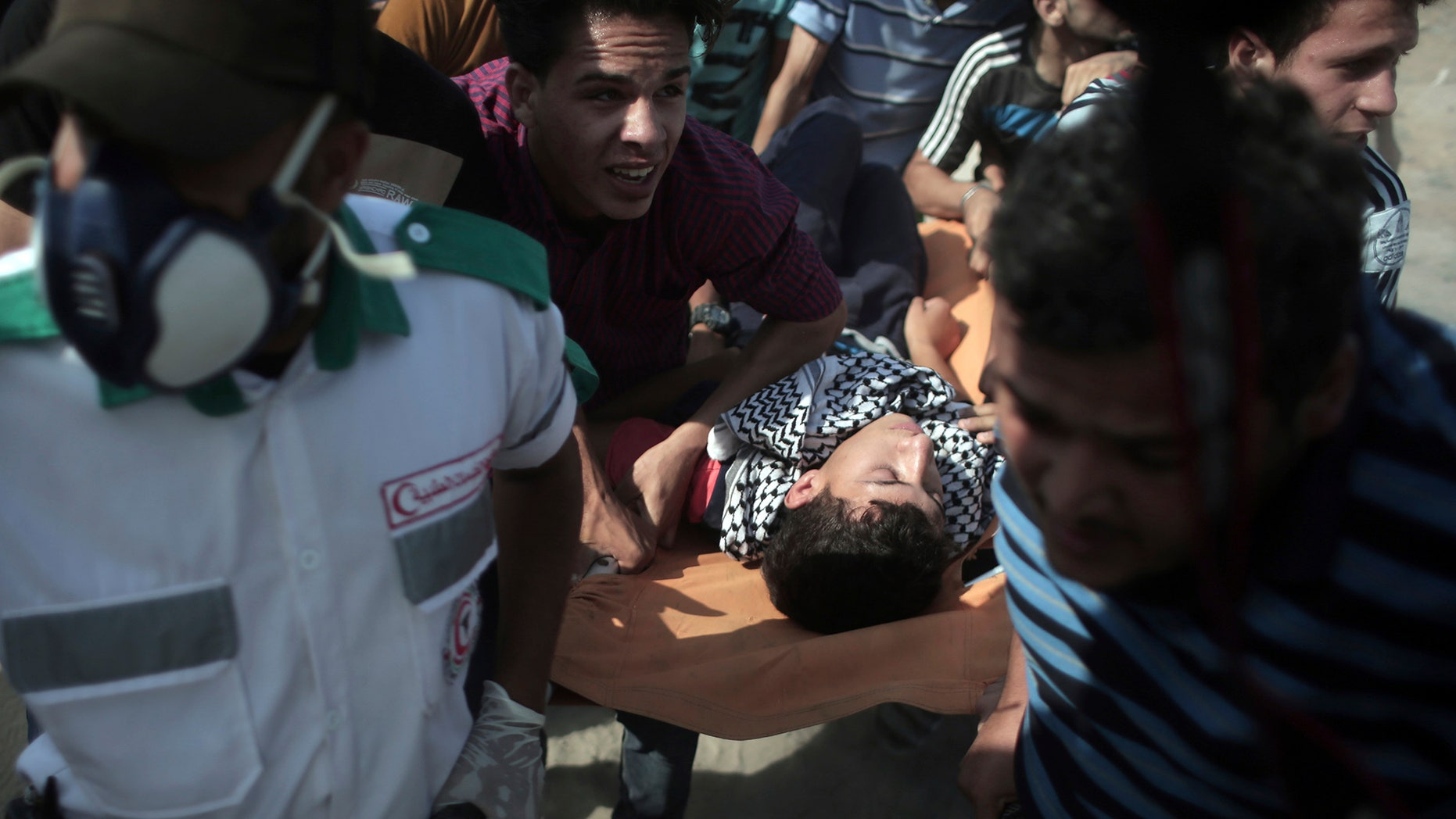 Palestinian medics and protesters evacuate an injured man during clashes with Israeli soldiers on the Israeli border with Gaza, Friday