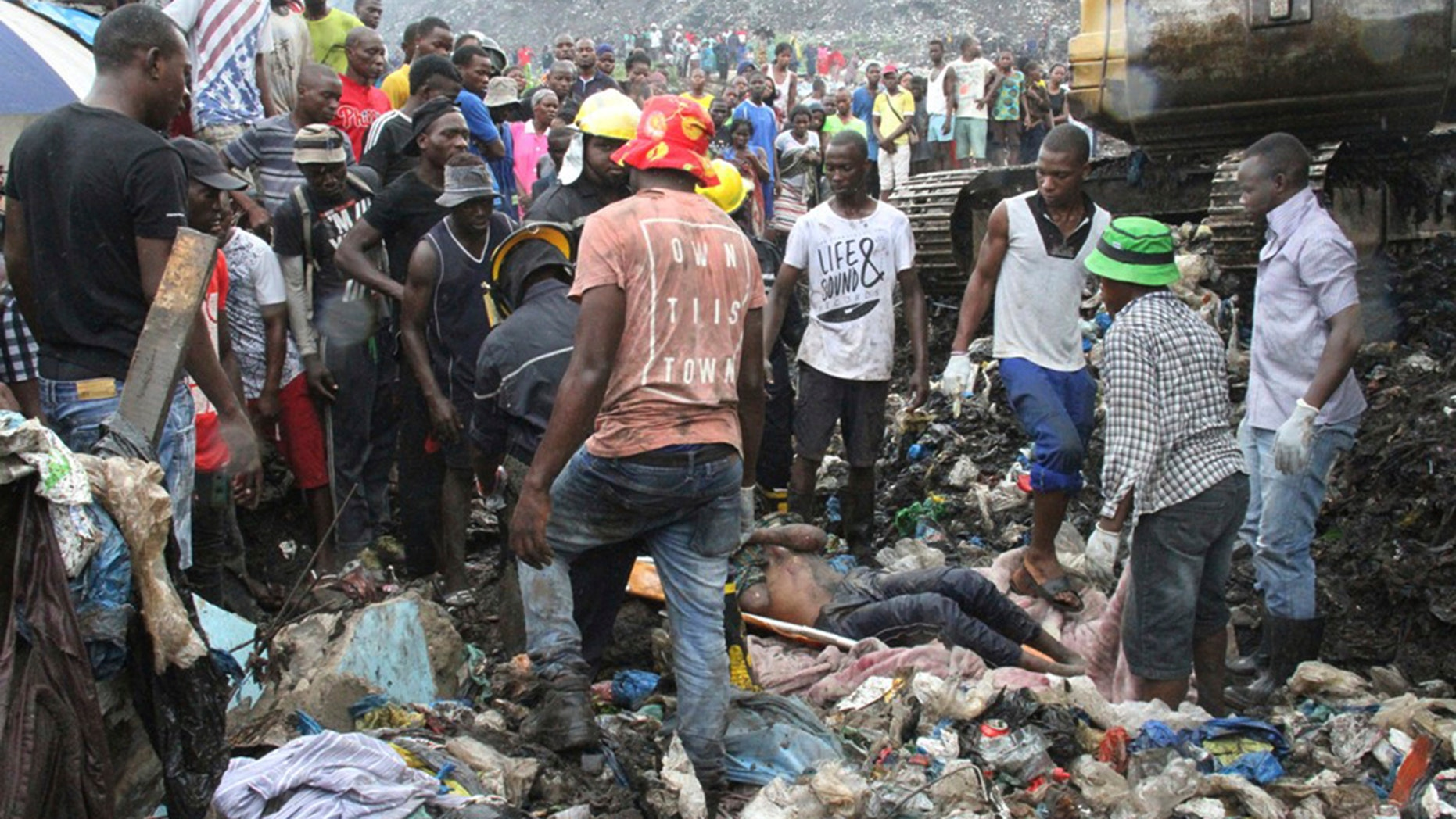 Rescuers recover a body as they search for survivors at the collapse of a garbage mound in Mozambique.